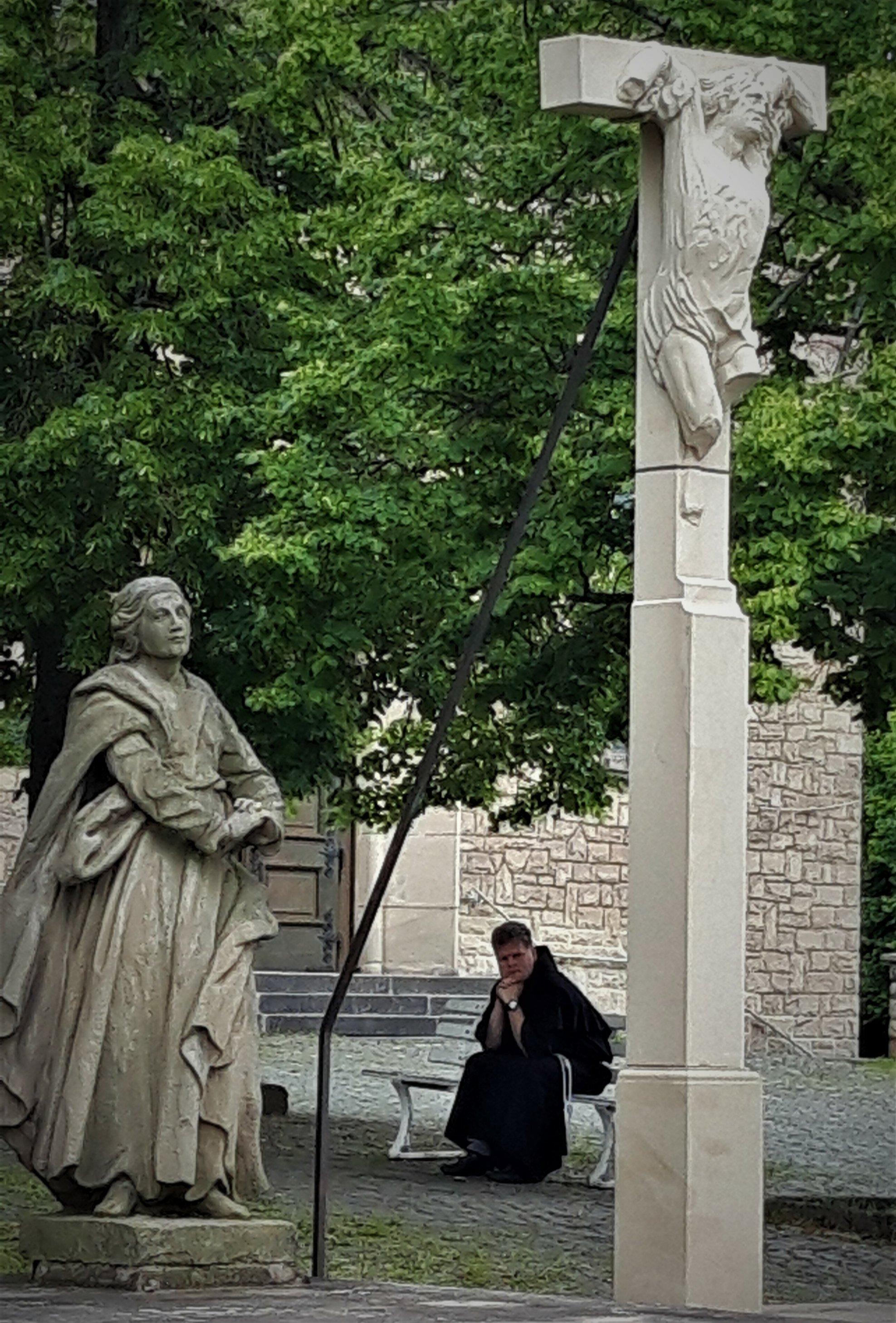 Zwischen zwei kirchlichen Standbildern ist der Blick frei auf einen Mönch in brauner Kutte und mit großer Uhr am Handgelenk, der, Kopf auf die Hände gestützt, auf einer Parkbank sitzt.