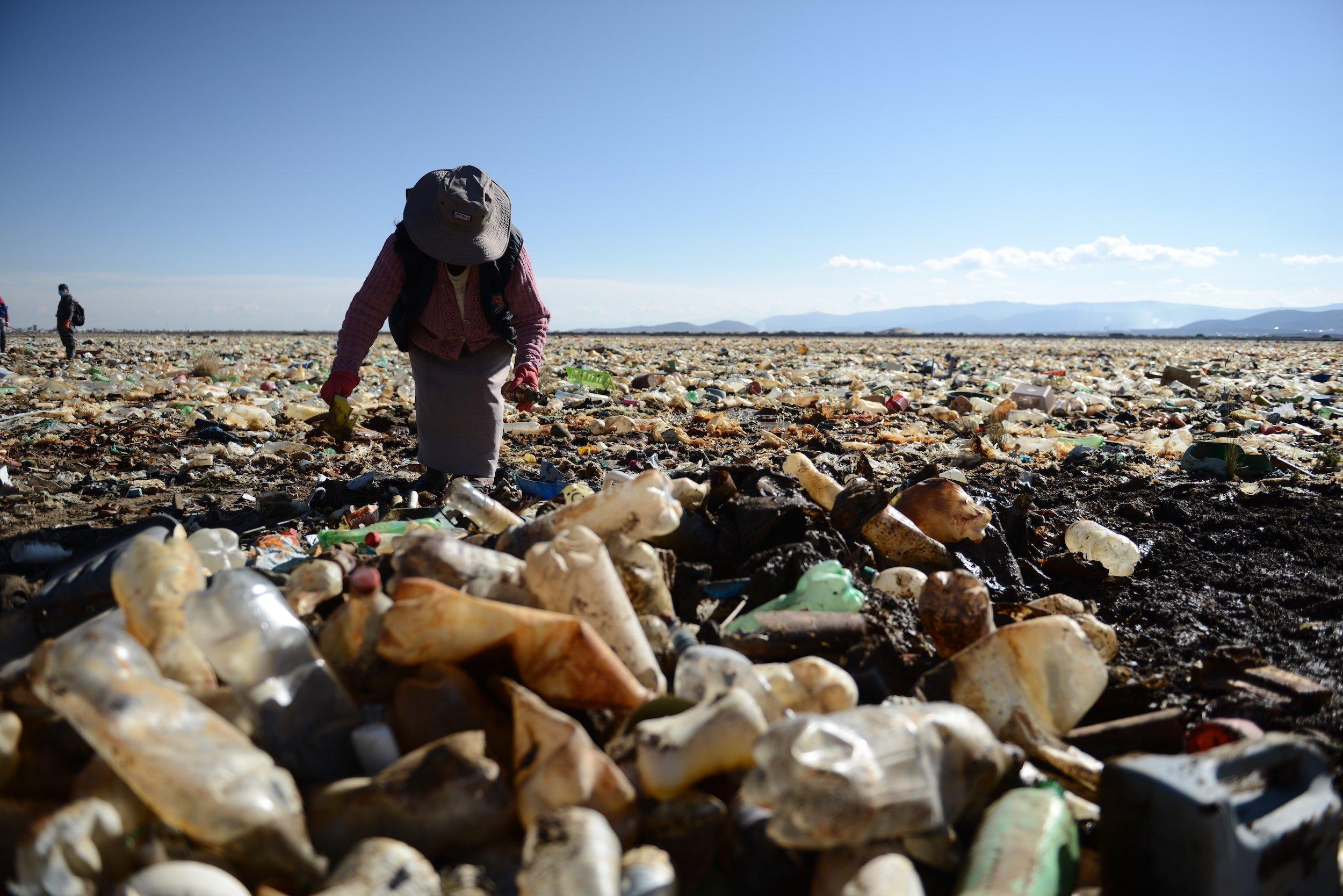Eine Frau mit Handschuhen nimmt an einer großangelegten Säuberungsaktion am verschmutzten Uru Uru-See teil.