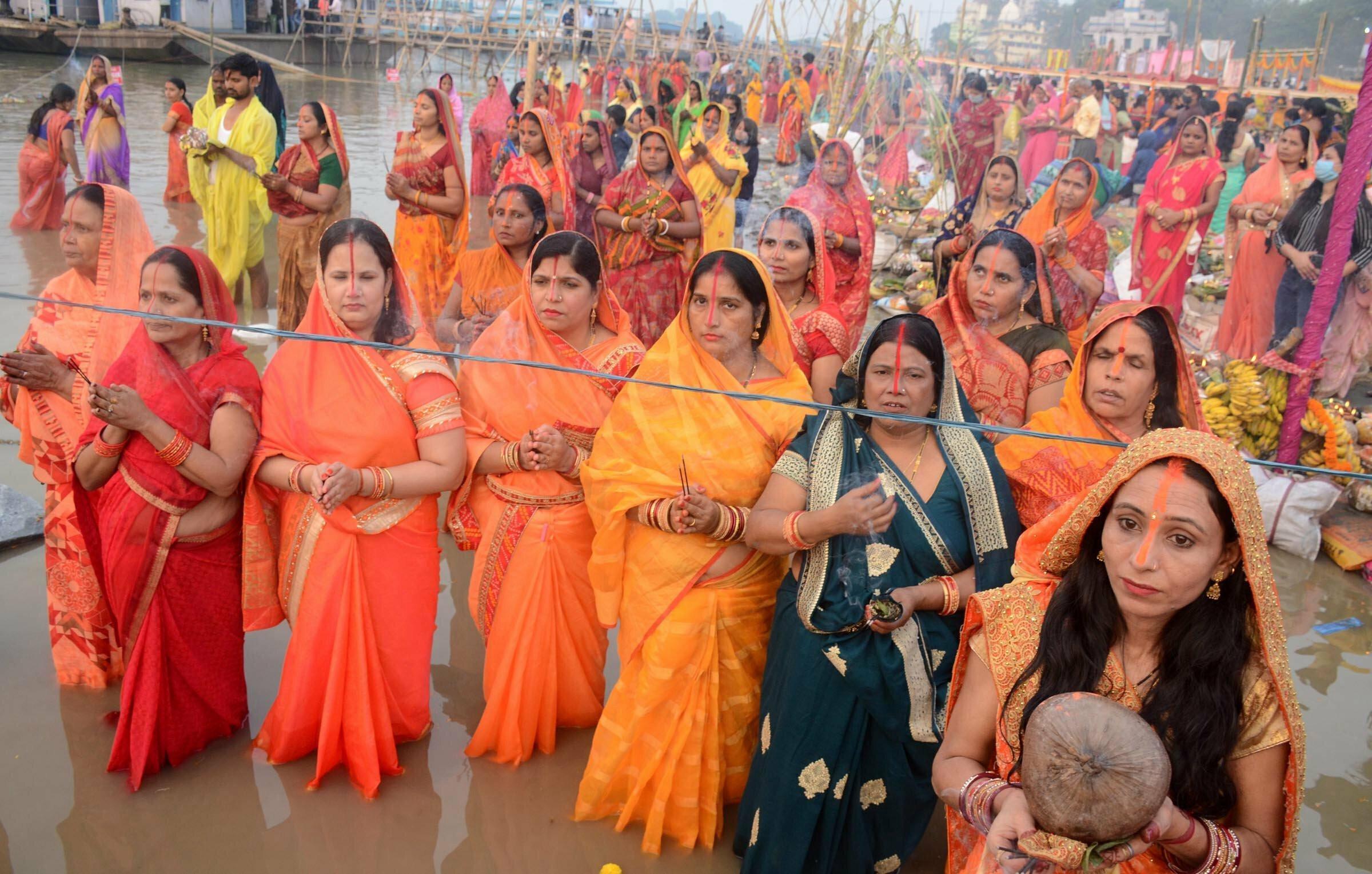 Frauen in orangefarbener und roter traditioneller Kleidung stehen im Wasser des Brahmaputra