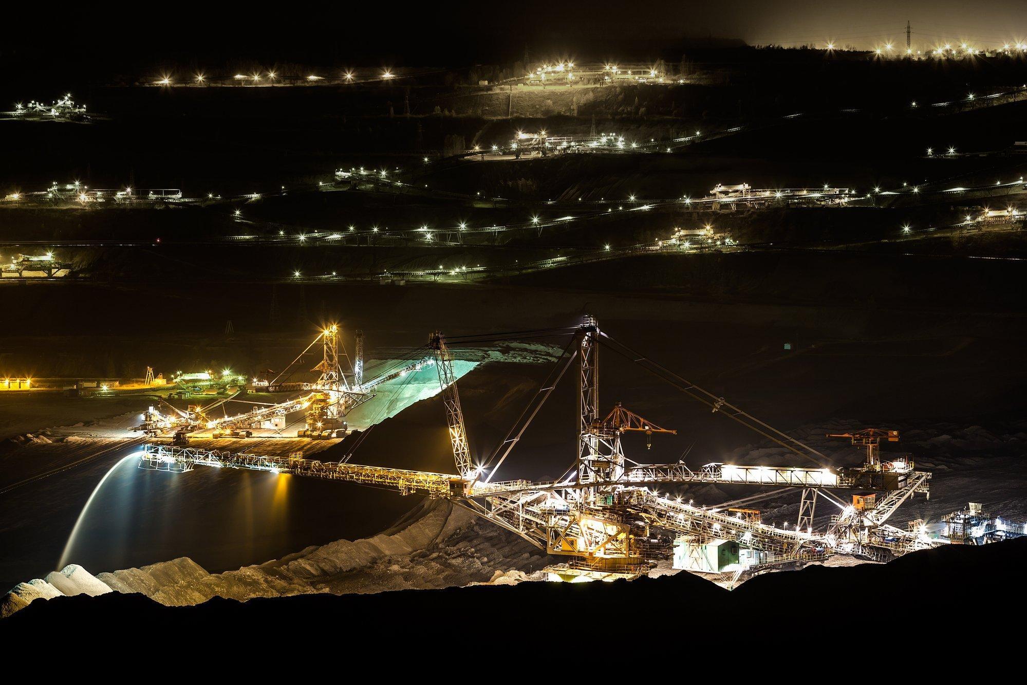 Kohletagebau bei Nacht, die riesigen Maschinen sind hell angestrahlt