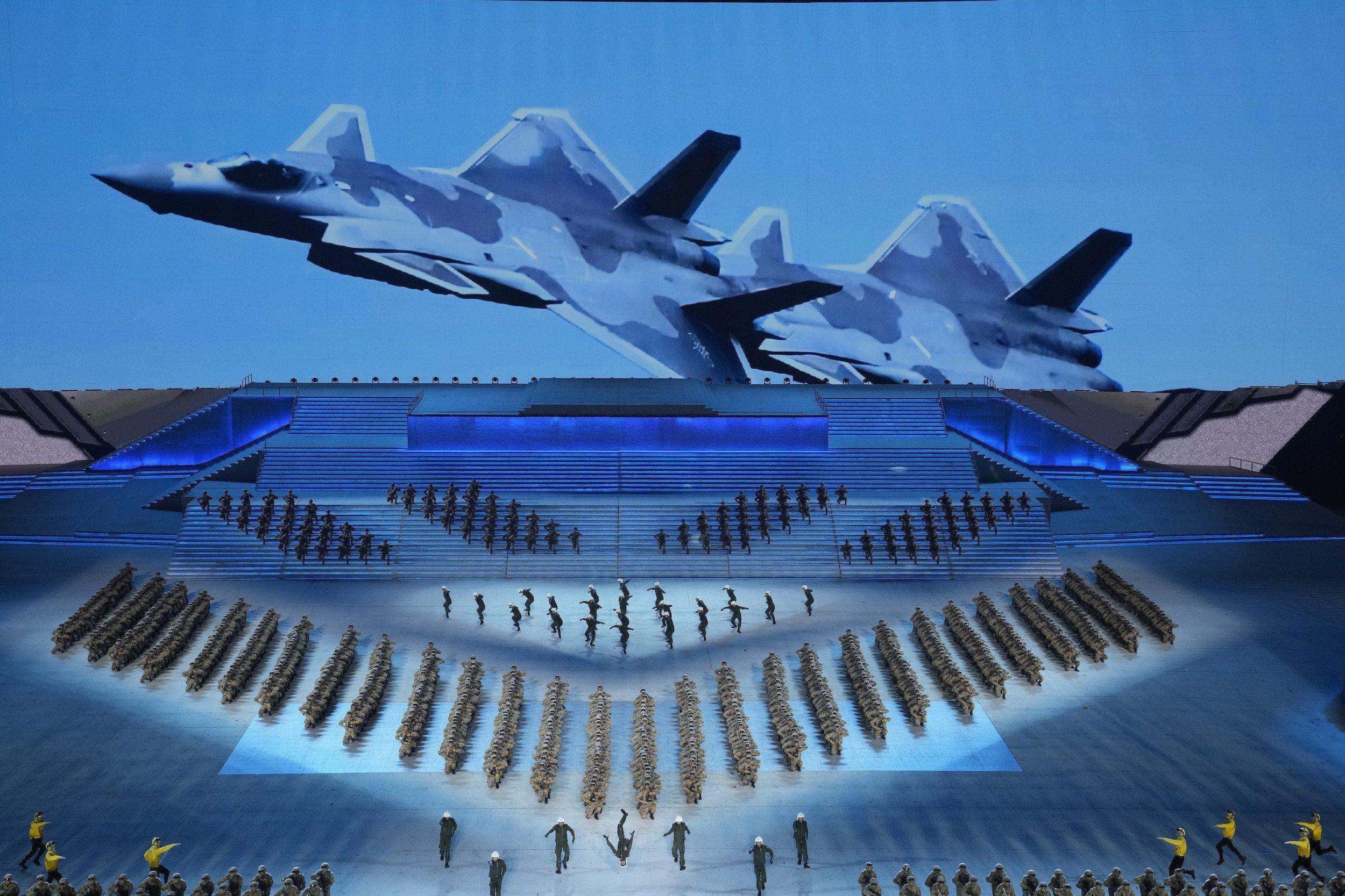Eine große Bühne in Blau mit Soldaten, die eine Aufführung bieten, an der Rückseite das Bild eines Kampfjets