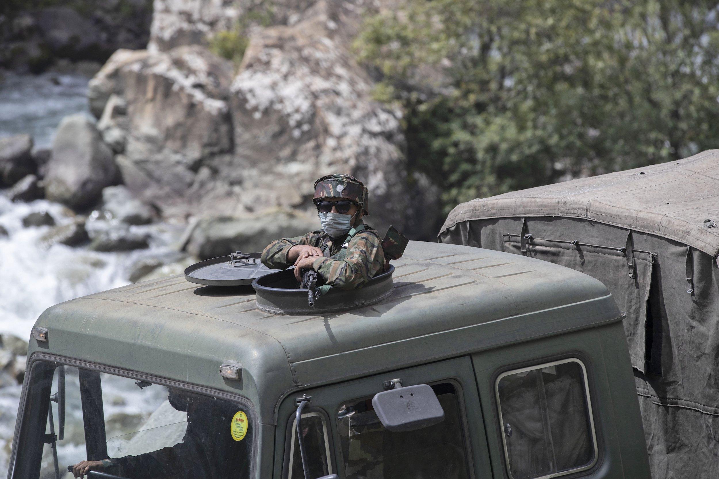 Ein maskierter indischer Soldat mit Gewehr schaut aus der Luke eines Militär-LKWs, das Fahrzeug steht an einem Fluss