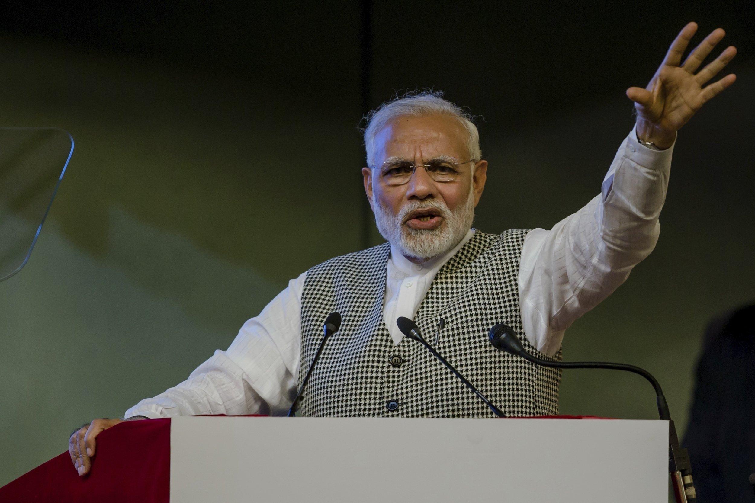 Modi am Rednerpult, er streckt seinen linken Arm nach oben