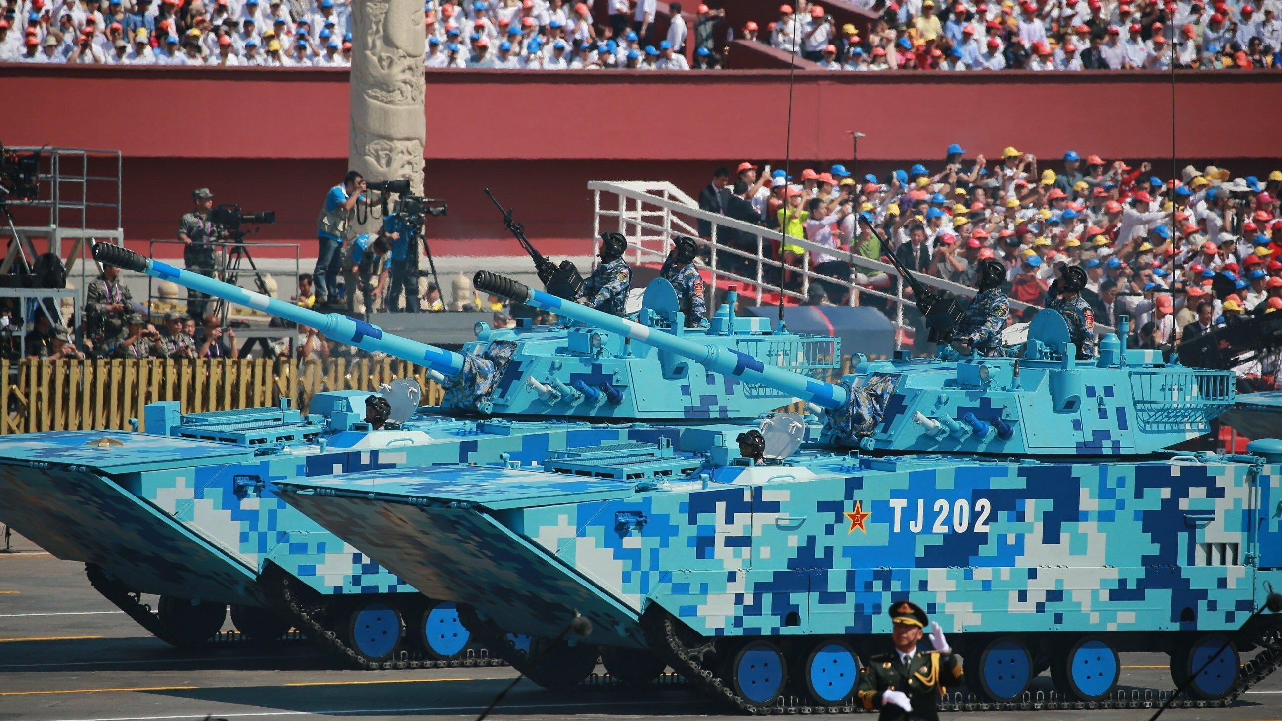 Zwei Panzer bei einer Militärparade, die nicht wie üblich grün, sondern in einem blauen Tarnmuster angestrichen sind.
