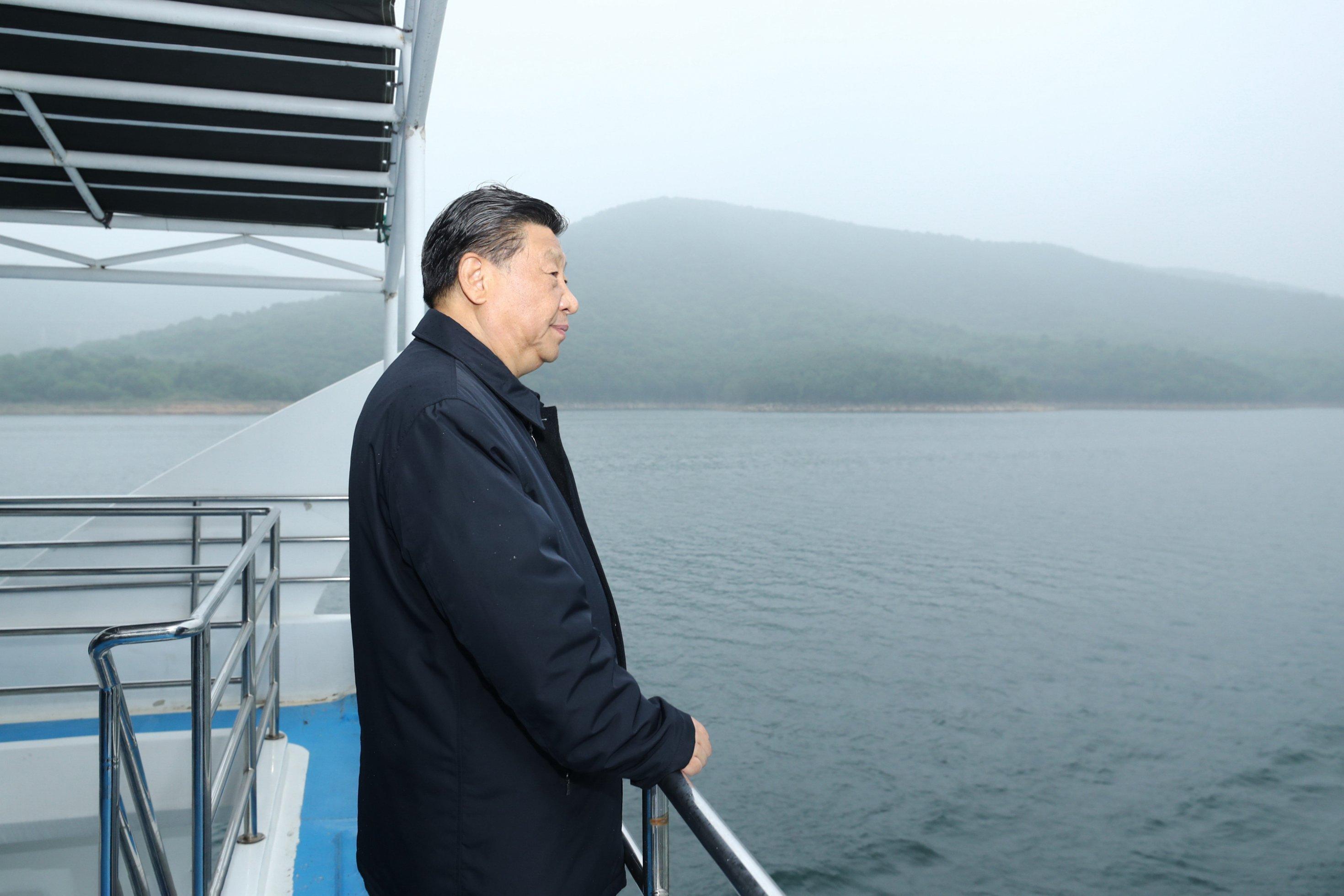 Xi Jinping steht an der Reling eines Bootes und schaut auf einen See.