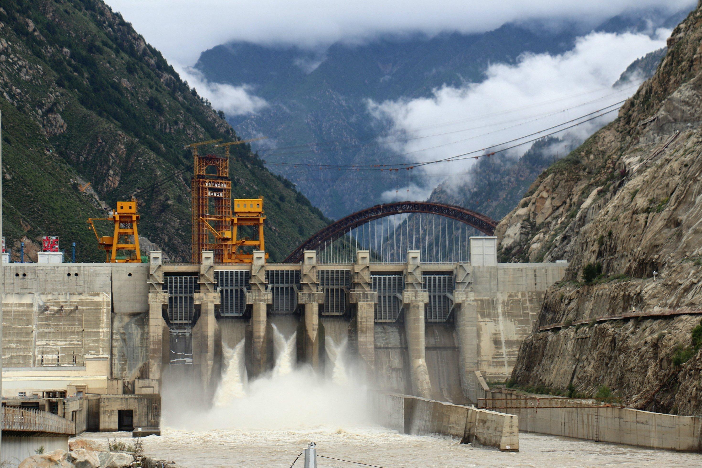 Großer Staudamm in einem engen Tal, Wasser schießt durch die Turbine