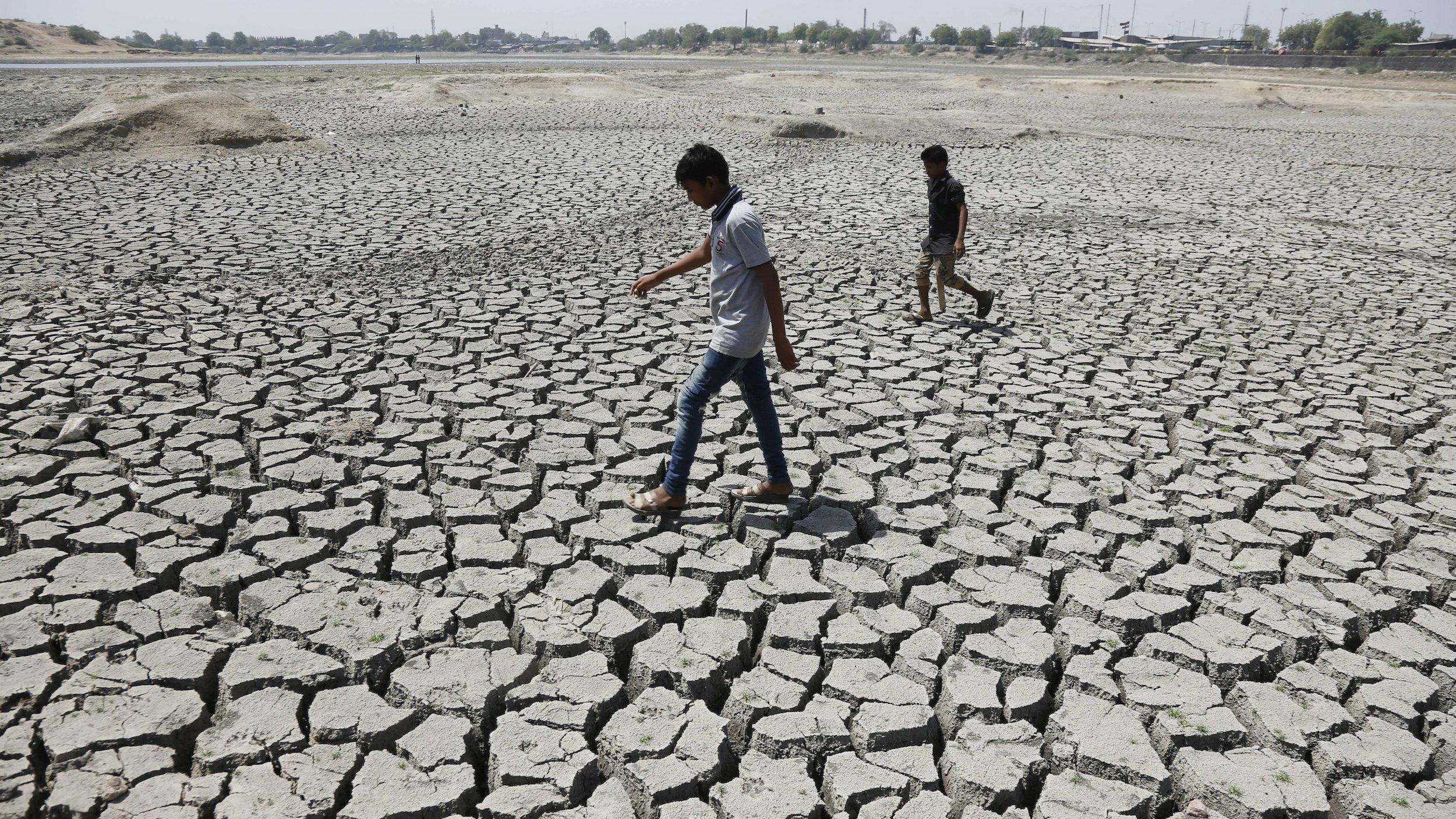 Zwei Männer laufen über den Grund eines ausgetrockneten Sees, dessen Boden durch die Trockenheit aufgeplatzt ist,