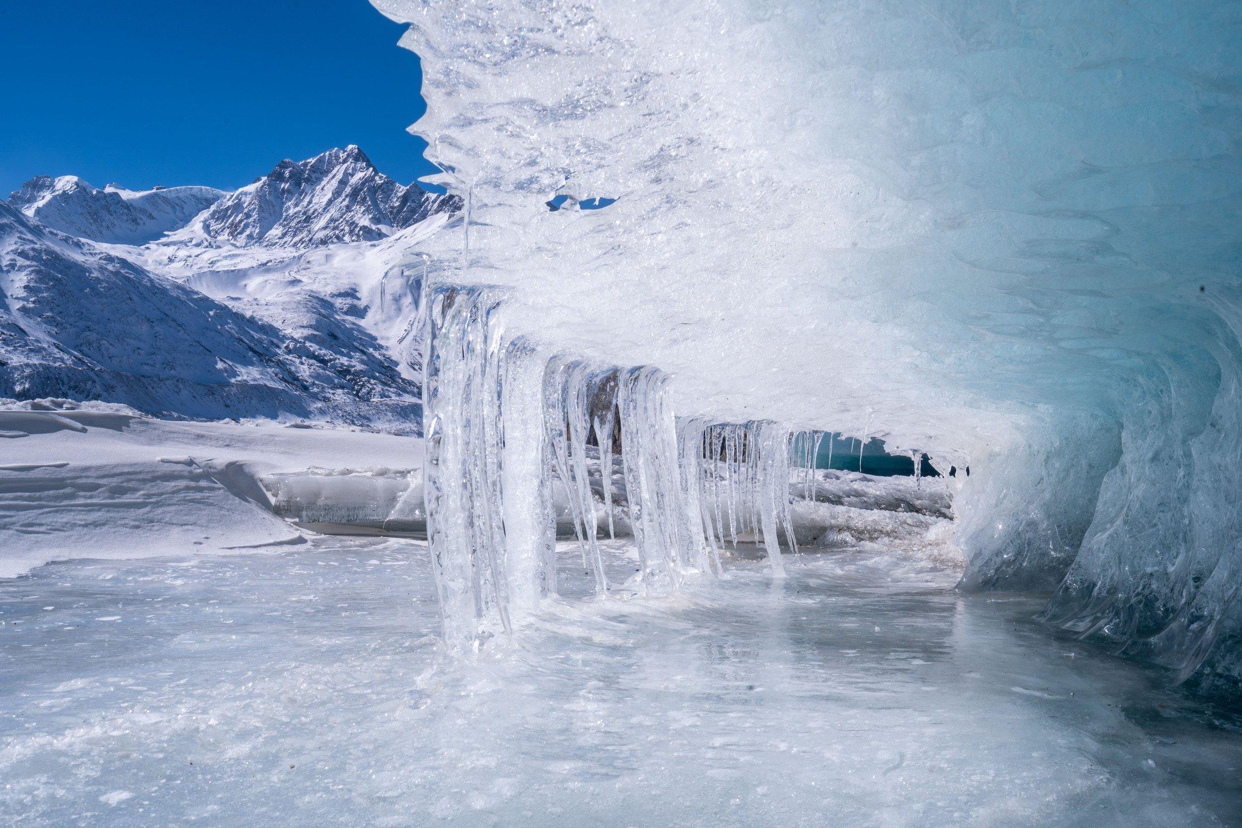 Eislandschaft im HImalaya, gefrorenes Schmelzwasser eines Gletschers formt sich zu einer Welle, im Hintergrund Berge.
