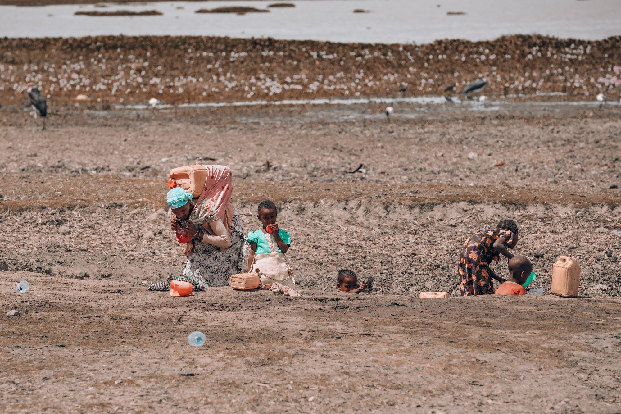 Eine Frau holt in Äthiopien mit ihren Kindern Wasser aus einem schlammigen Loch.