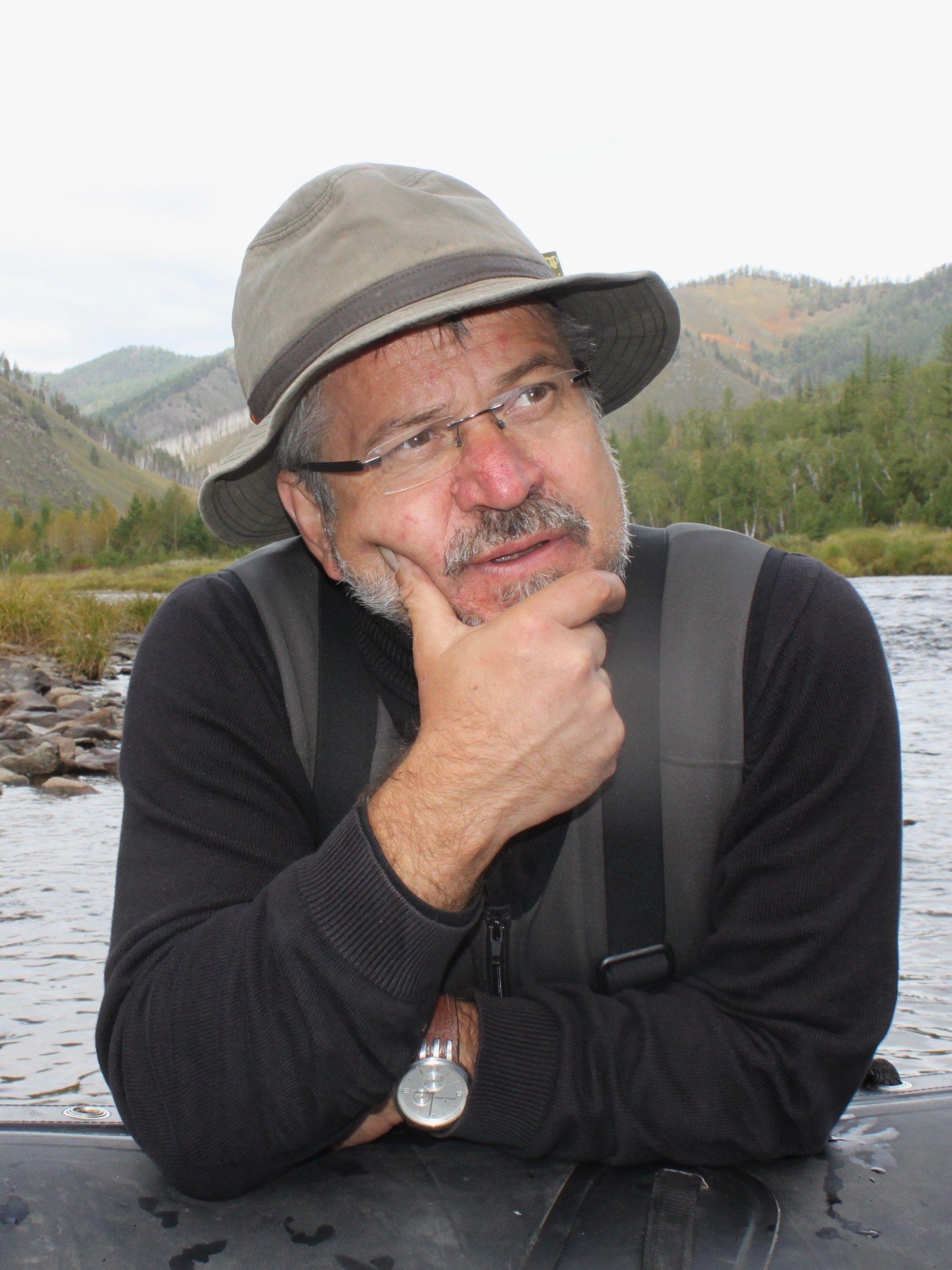 Dietrich Borchardt sitzt mit grübelnder Miene an einem Tisch im Freien, im Hintergrund Wasser.