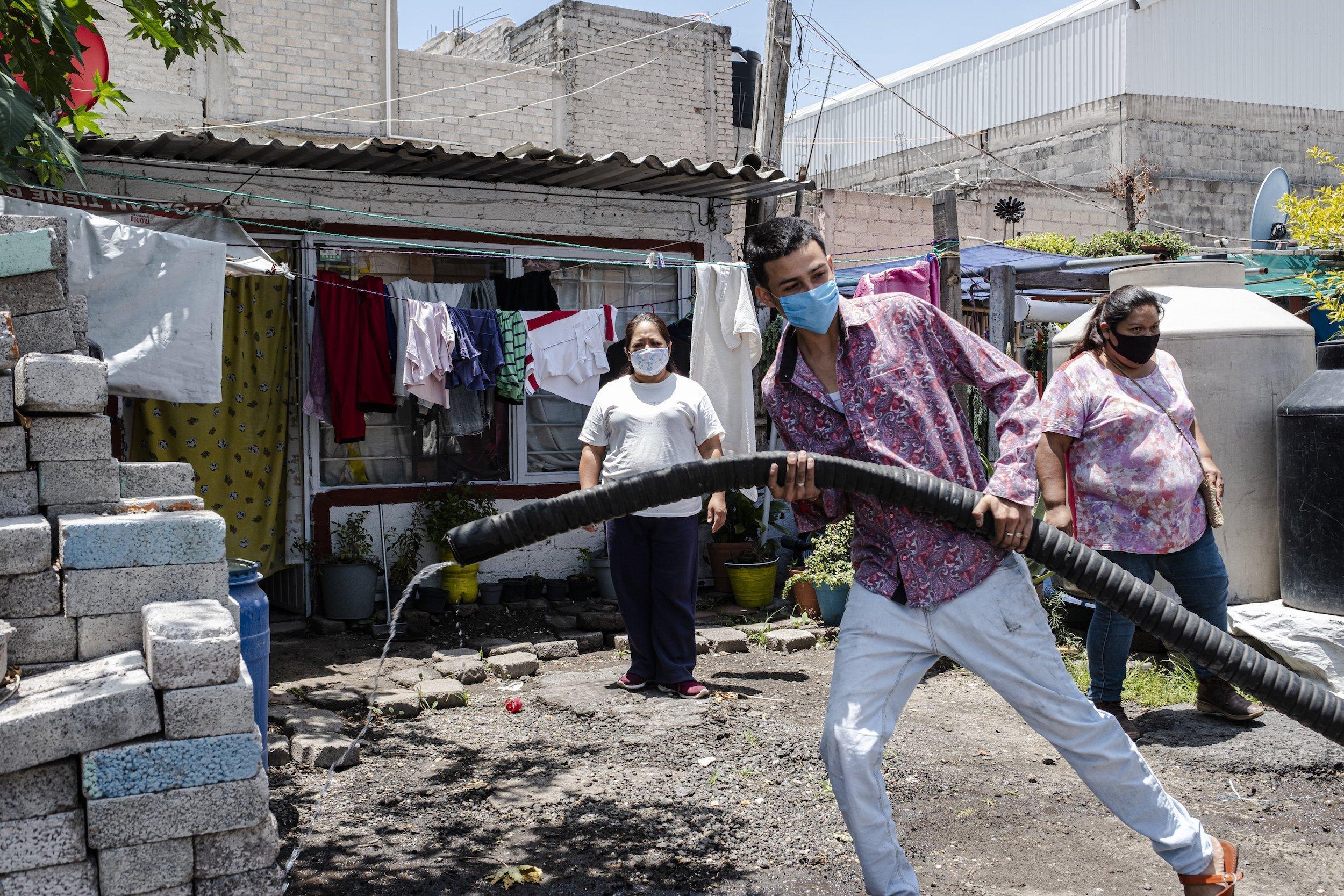 Ein junger Mann in einem mexikanischen Armenviertel zieht einen großen Wasserschlauch, um einen Behälter zu befüllen.