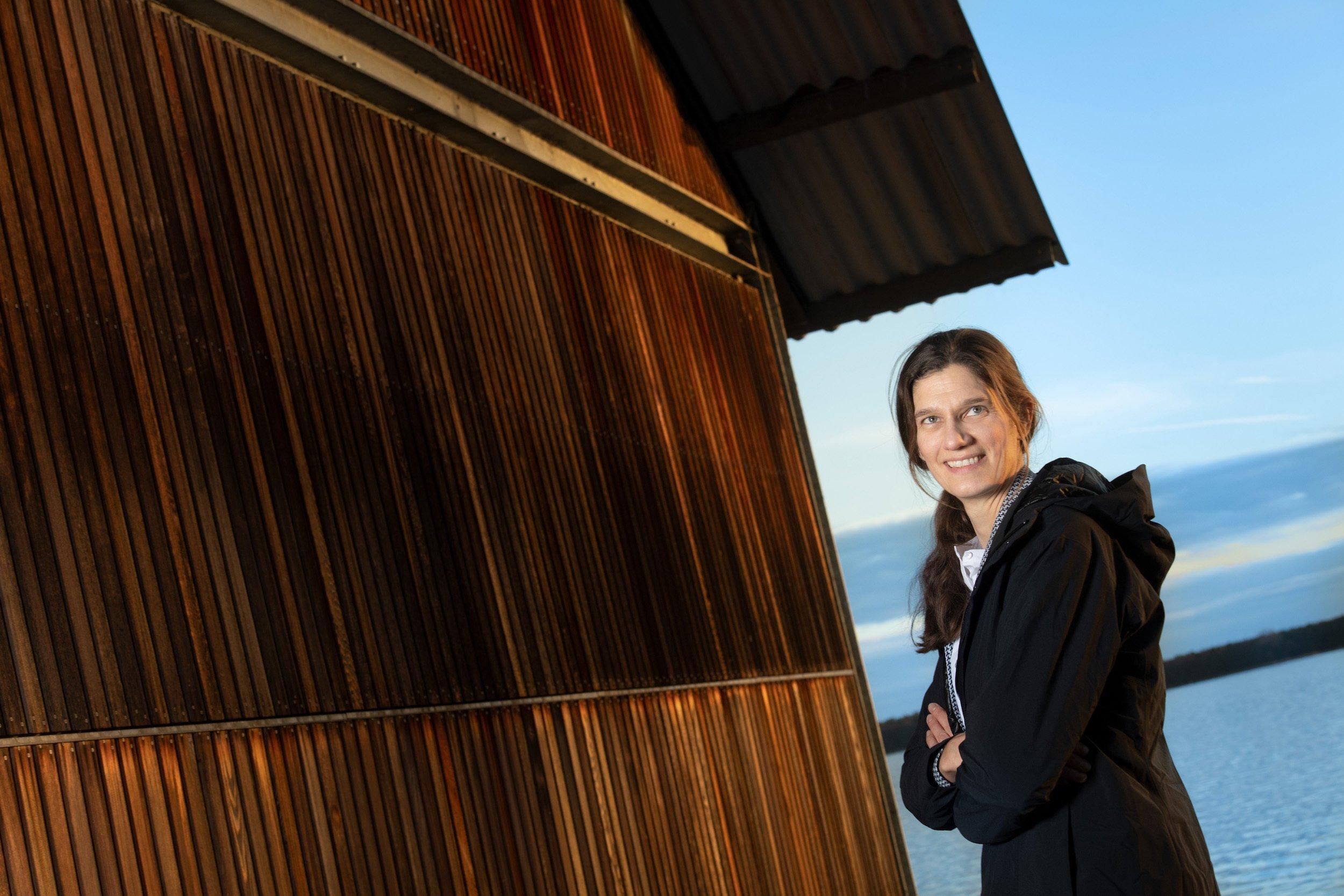 Sonja Jähnig vor einer Hütte an einem See.