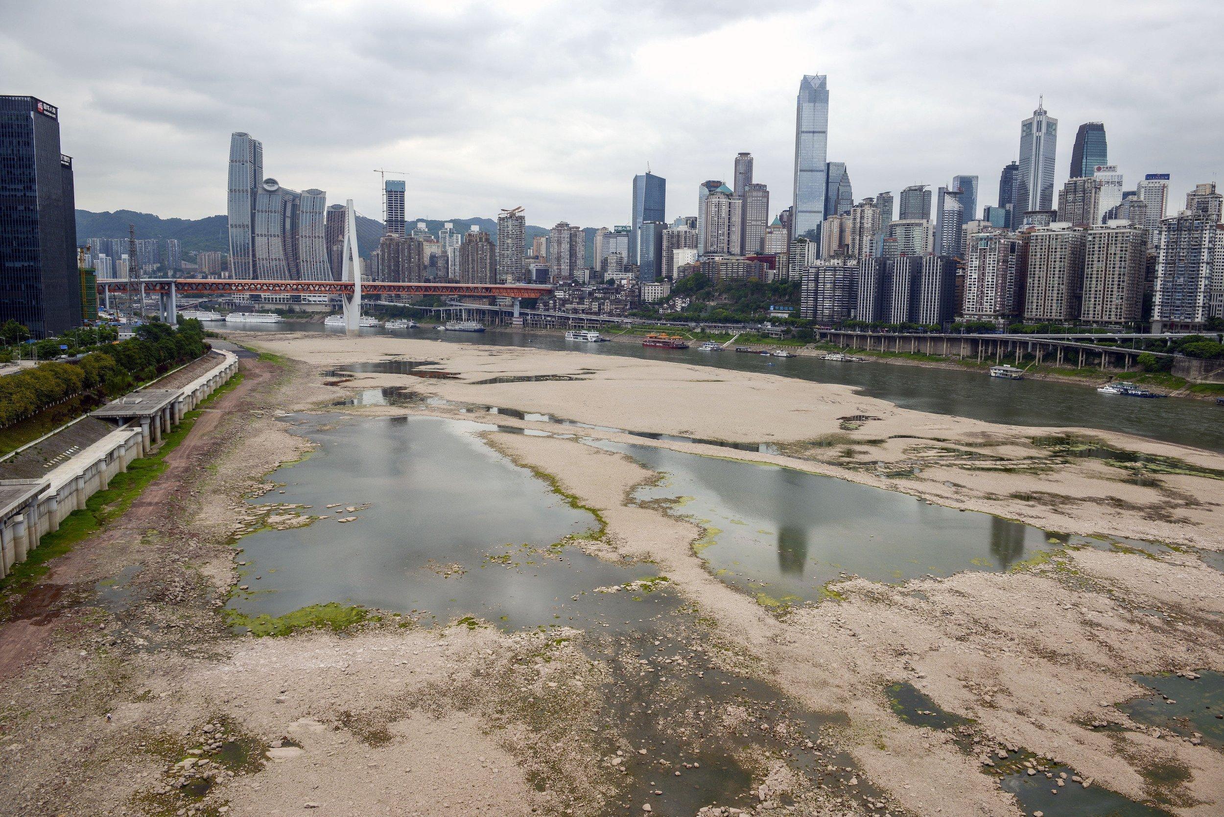 Zwischen den Hochhäusern fliesst statt eines mächtigen Flusses wegen Dürre nur ein Rinnsal.