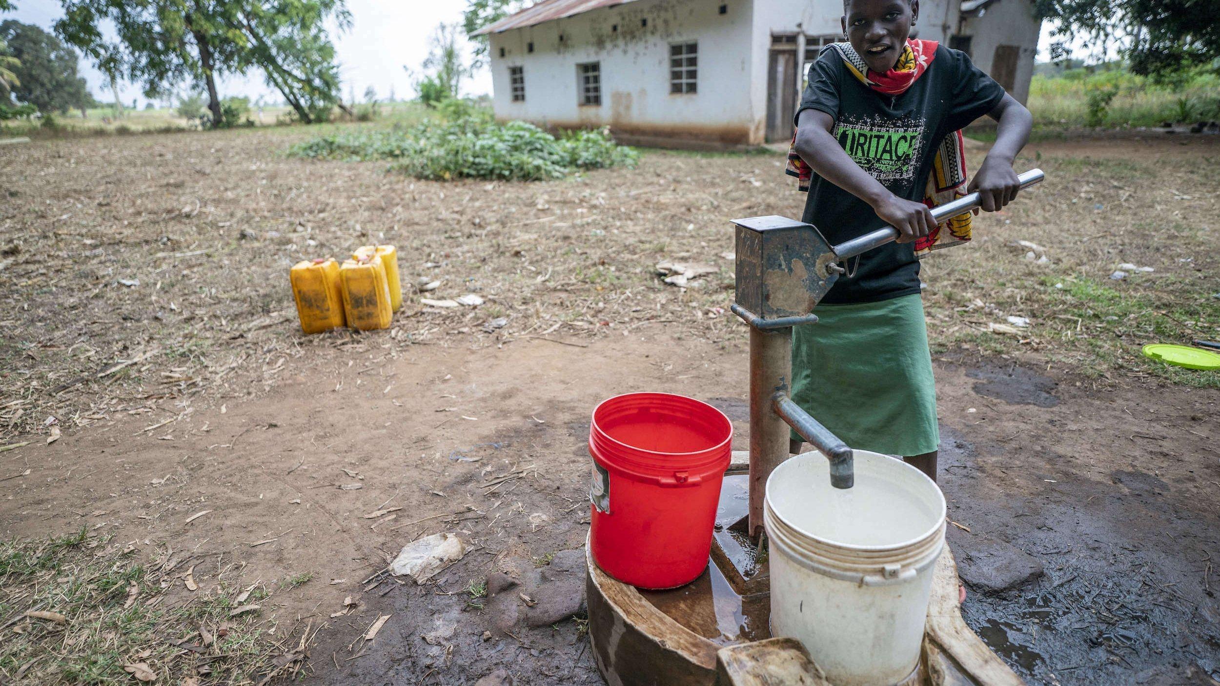 Eine junge Frau holt sich Trinkwasser mit einer sehr einfach gebauten Pumpe. Hinter ihr ein sehr ärmlich wirkendes Haus.