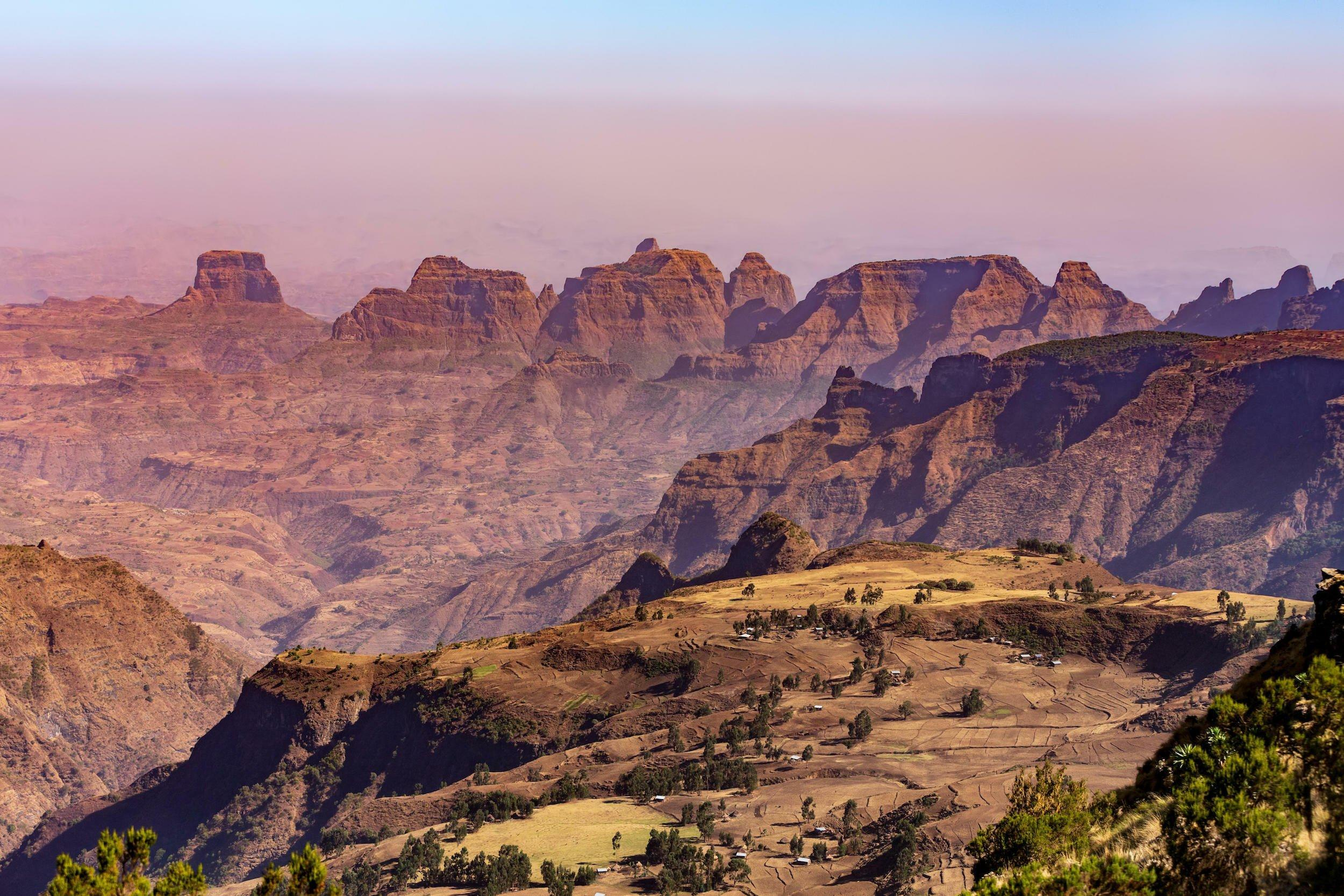 Eine trockene Gebirgslandschaft mit zackigen Gipfeln, im Vordergrund eine kleine bäuerliche Siedlung.