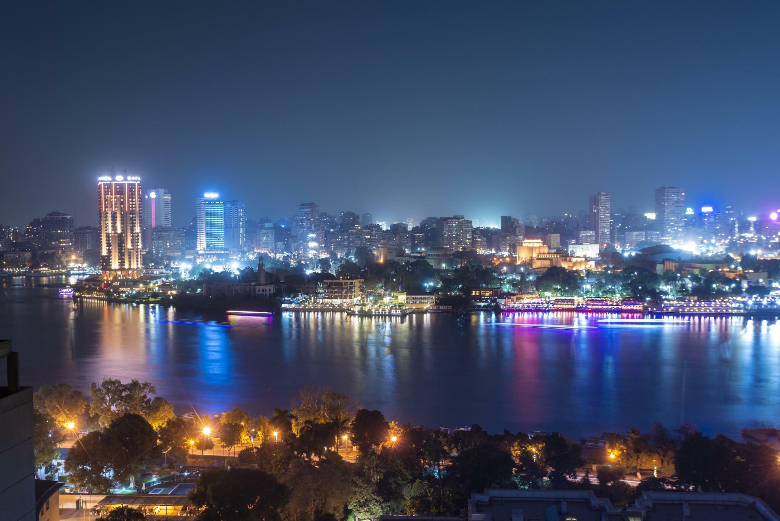 Die Skyline von Kairo bei Nacht mit dem Nil im Vordergrund.