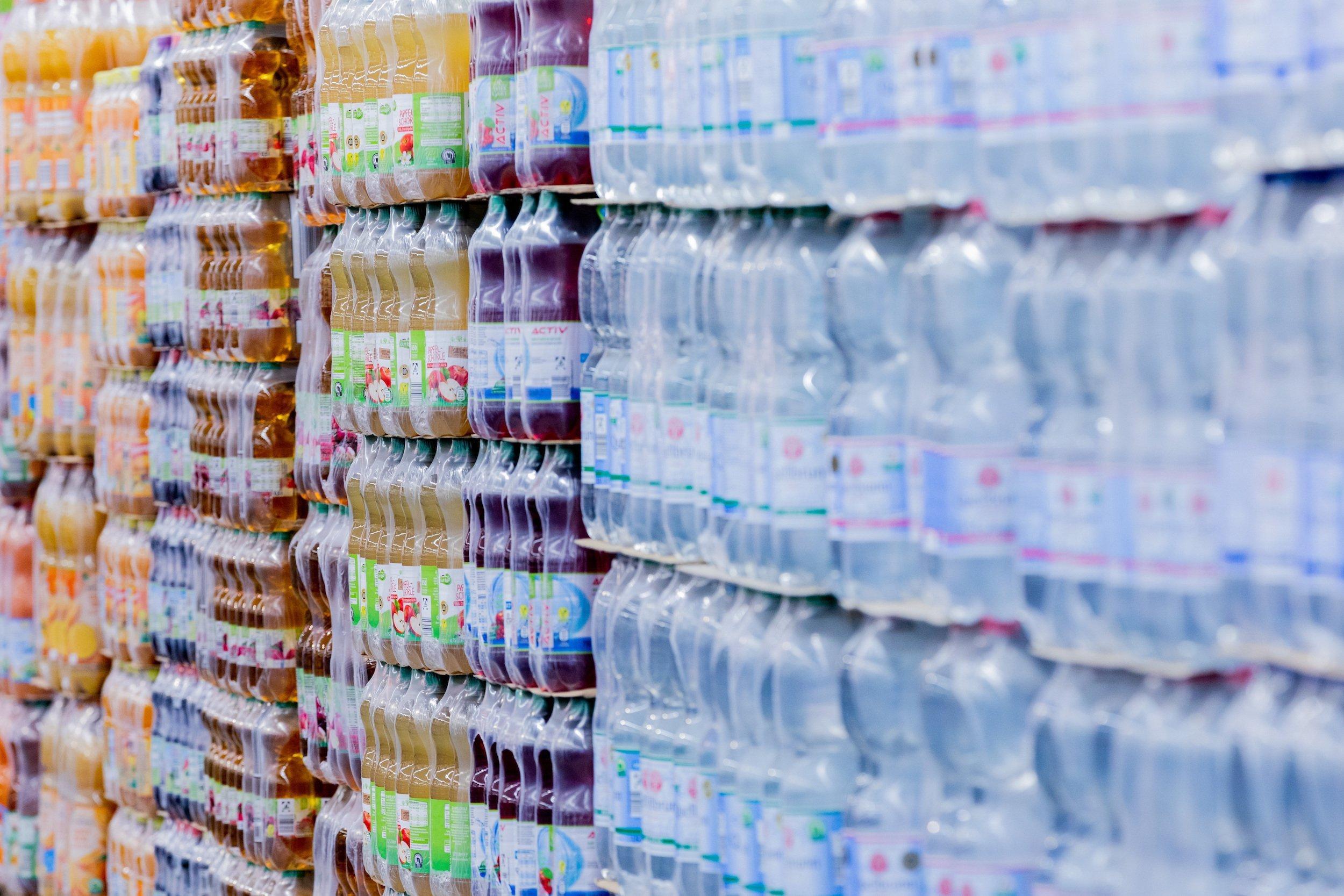 Plastikflaschen bis zur Decke gestapelt im Supermarkt.