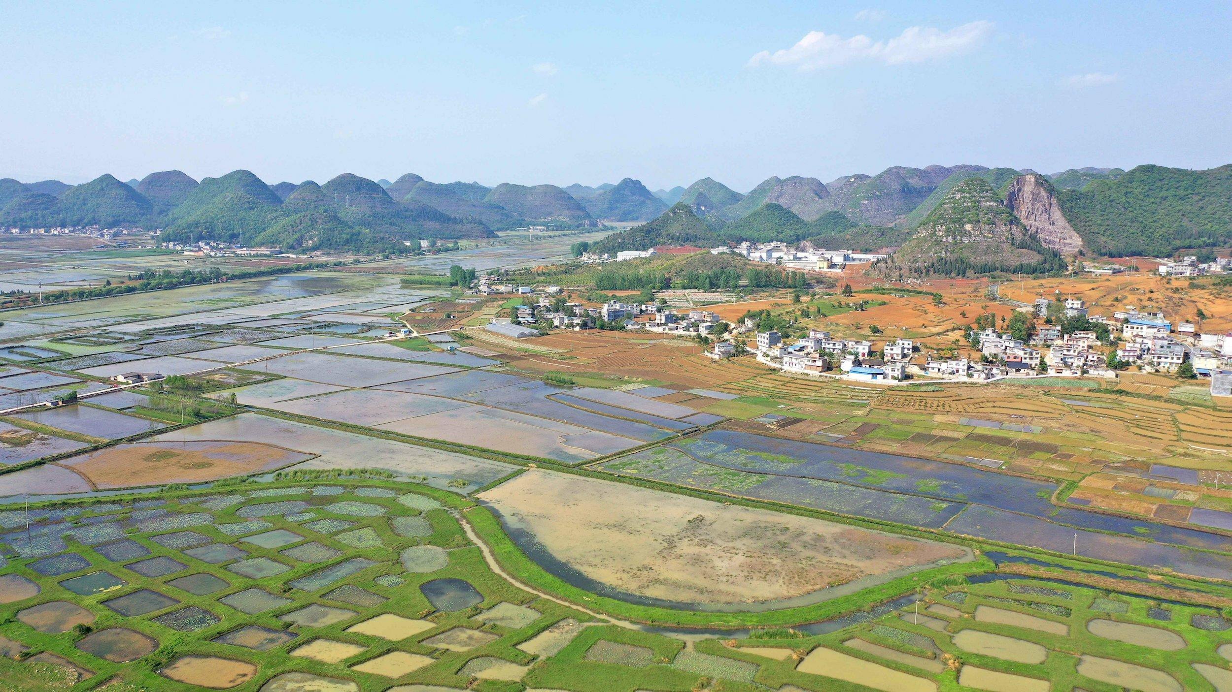 Eine Landschaft mit zahlreichen kleinen Tümpeln vor einem Dorf und Hügeln.