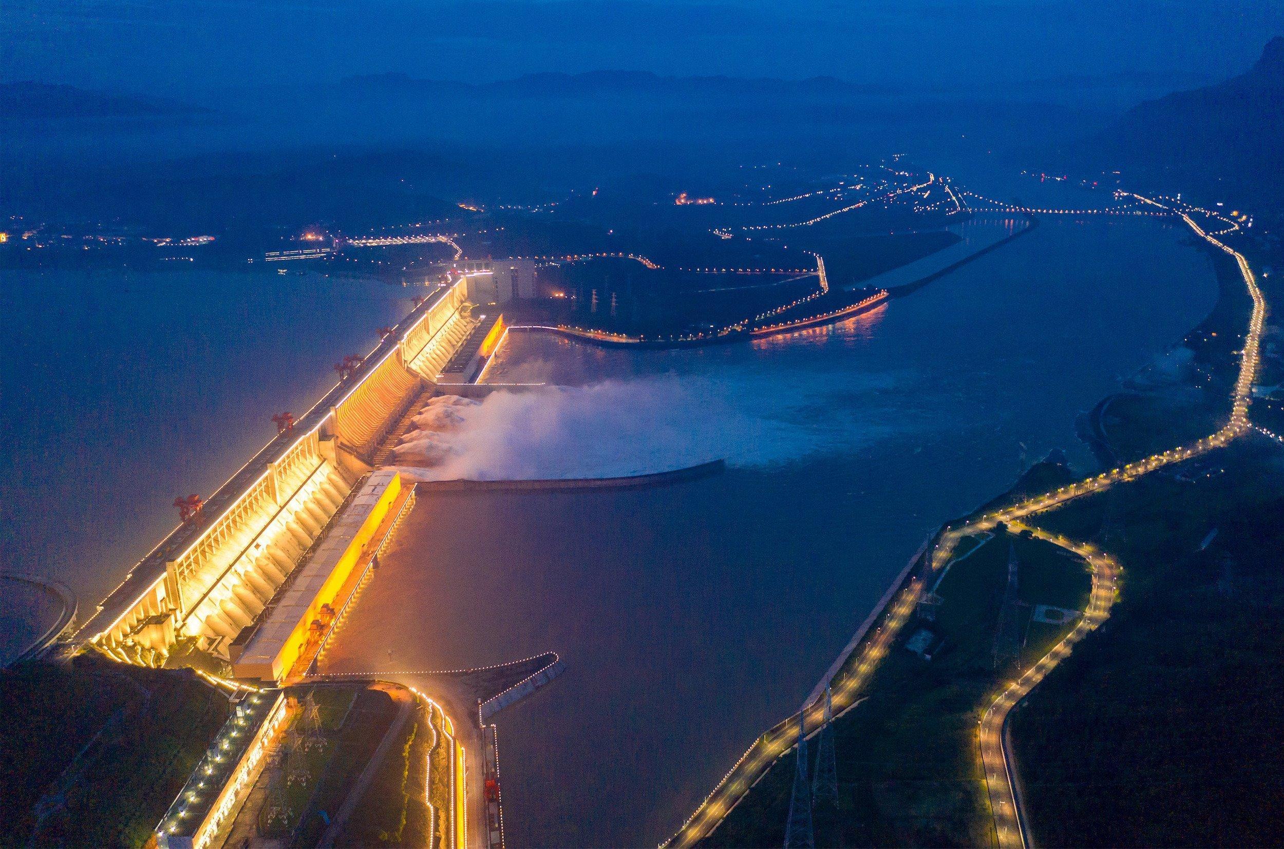 Eine Luftaufnahme des riesigen Drei-Schluchten-Staudamms bei Nacht.  Der Staudamm ist hell erleuchtet.