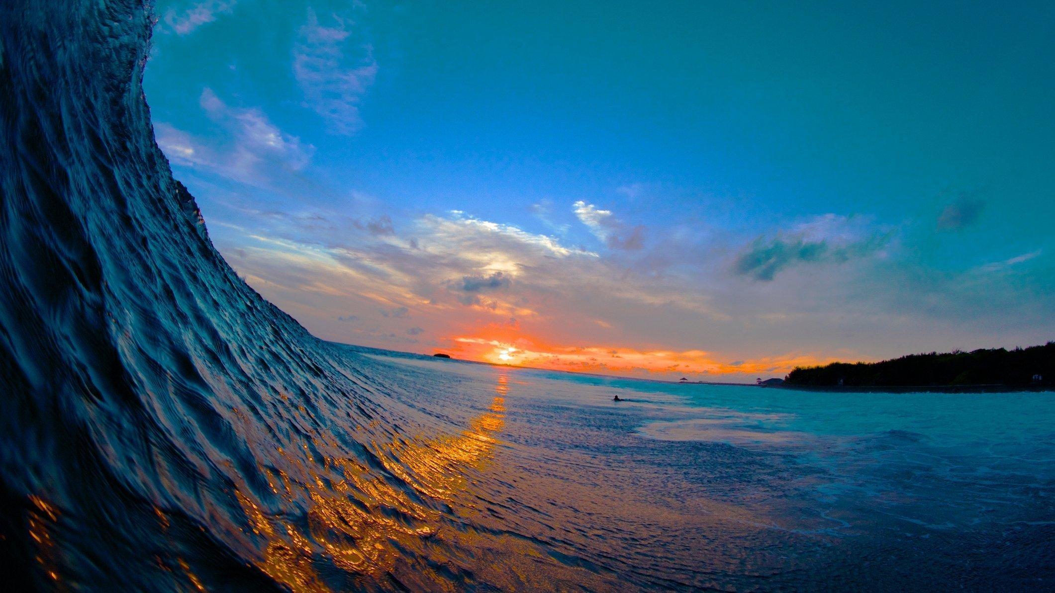 Vor dem Sonnenuntergang türmt sich eine große Welle auf.