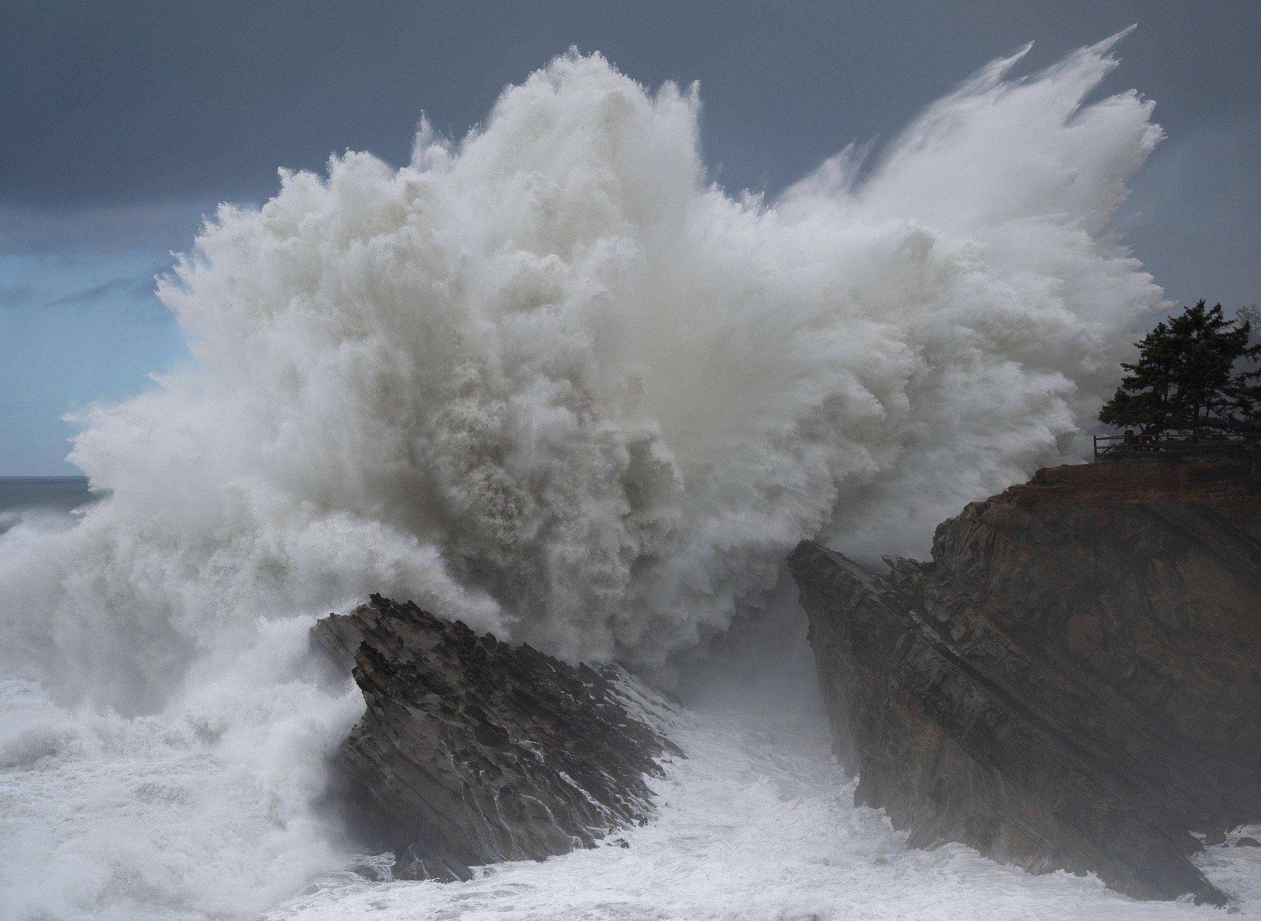 Das Bild zeigt, wie eine Welle voller Kraft gegen Felsen kracht.