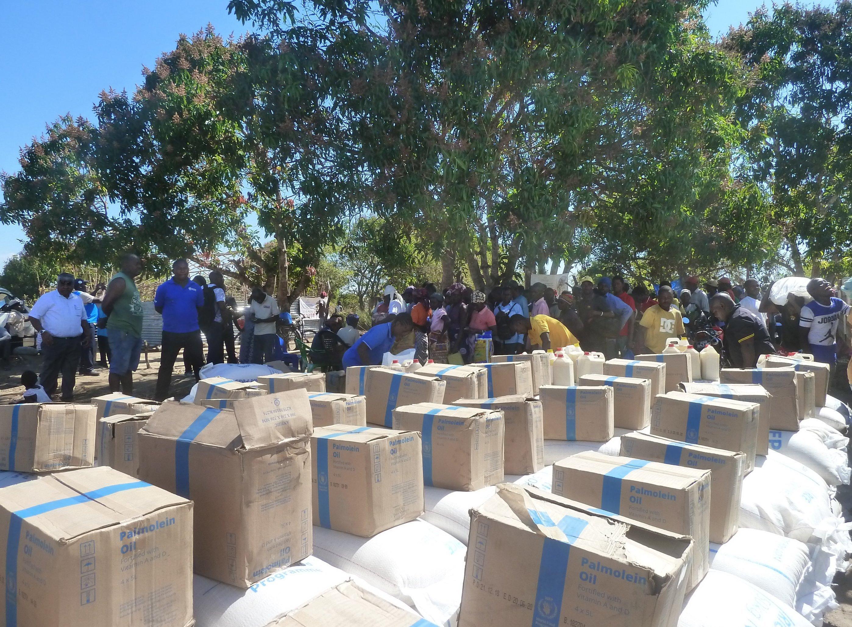 Das Bild zeigt Säcke und Kisten mit Lebensmitteln, die gerade von einem LKW des Welternährungsprogramms abgeladen wurden. Drumherum warten bereits die Hilfsbedürftigen. Mosambikanerinnen, die durch den Zyklon 2019alles verloren haben.
