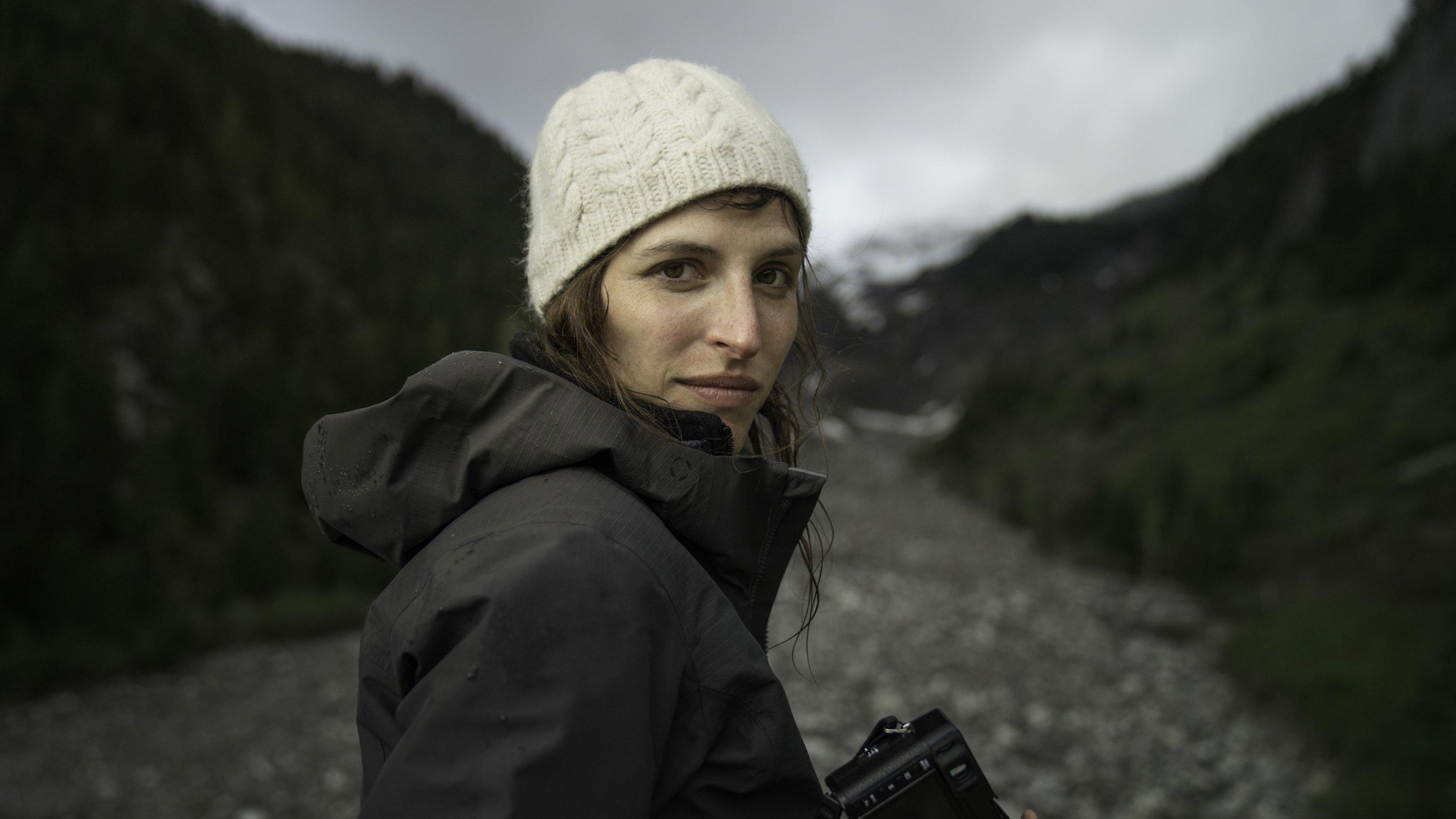 Die junge Frau ist dem Betrachter halb zugewandt, hat eine Kamera in der Hand und eine Wollmütze auf dem Kopf.