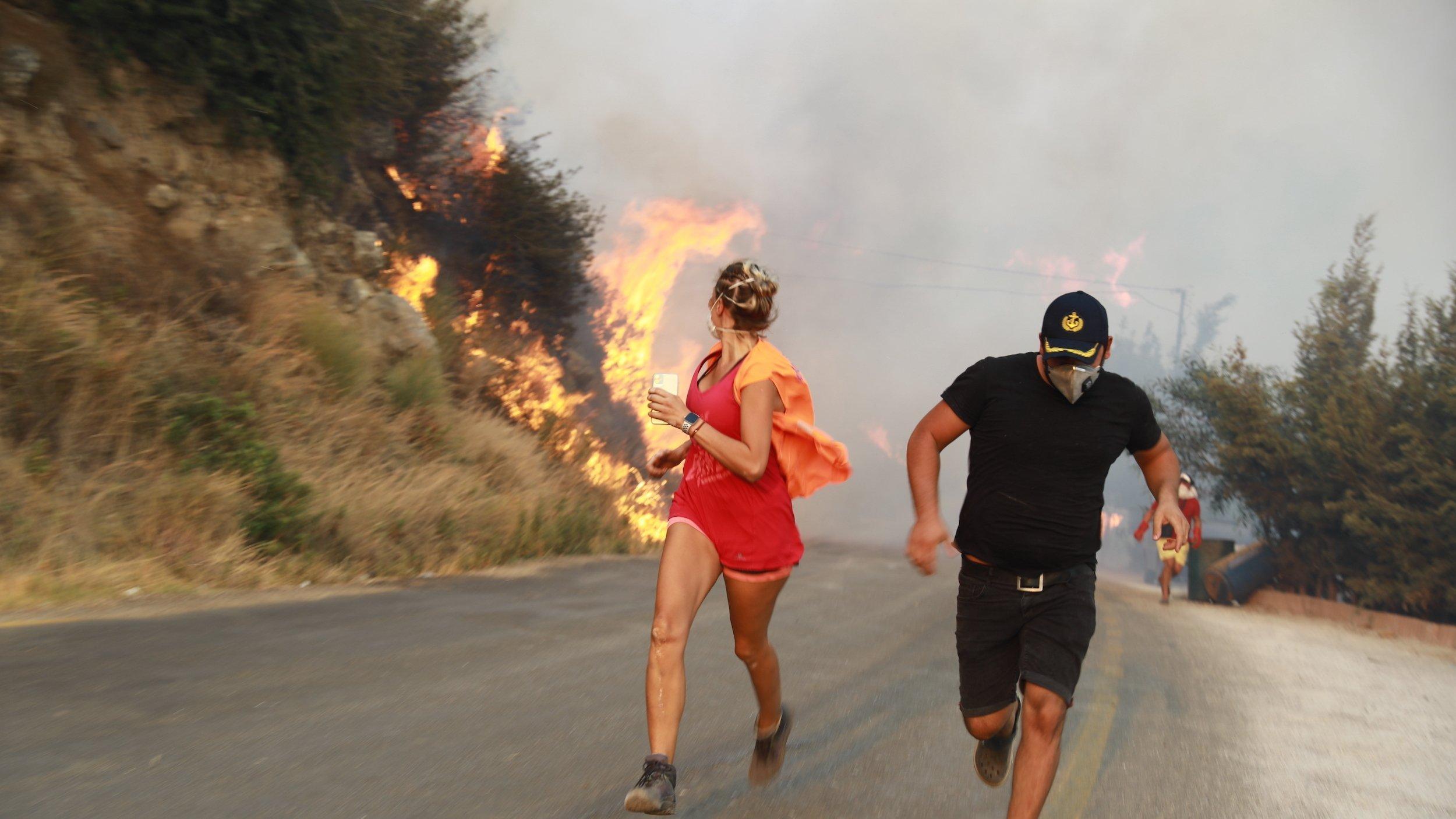 Ein Mann und eine Frau laufen auf einer Landstraße vor dem Feuer davon
