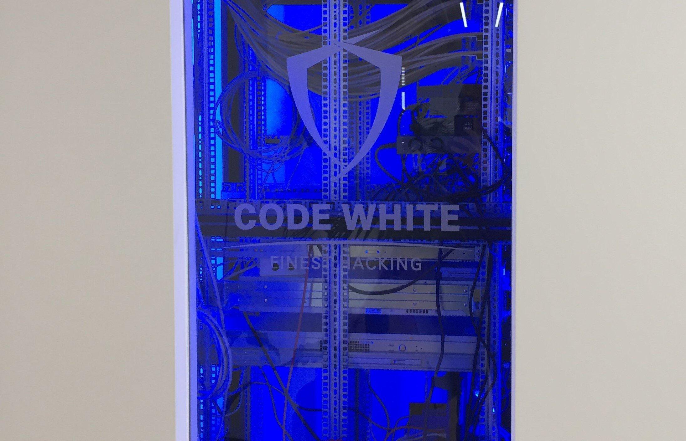 Ein großer Serverschrank, auf dessen Glastür das Firmenlogo eingraviert ist, wurde in eine weiße Wand eingelassen. Das Innere des Schrankes ist komplett in kaltes blaues Licht getaucht. In ihm befindet sich, umgeben von einer Menge Kabel, ein wuchtiger Hochleistungscomputer in einem unspektakulären Metallgehäuse.