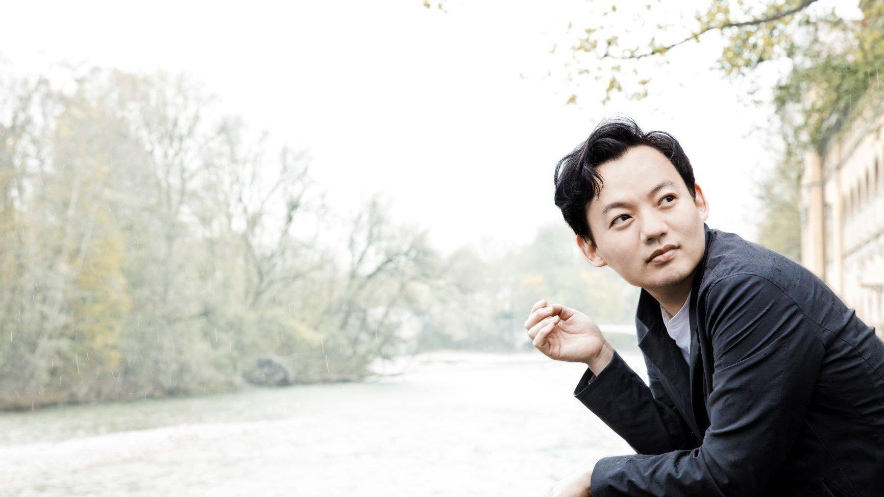 Der junge, in Seoul geborene Pianist William Youn steht auf eine Mauer gestützt an einem Fluss.