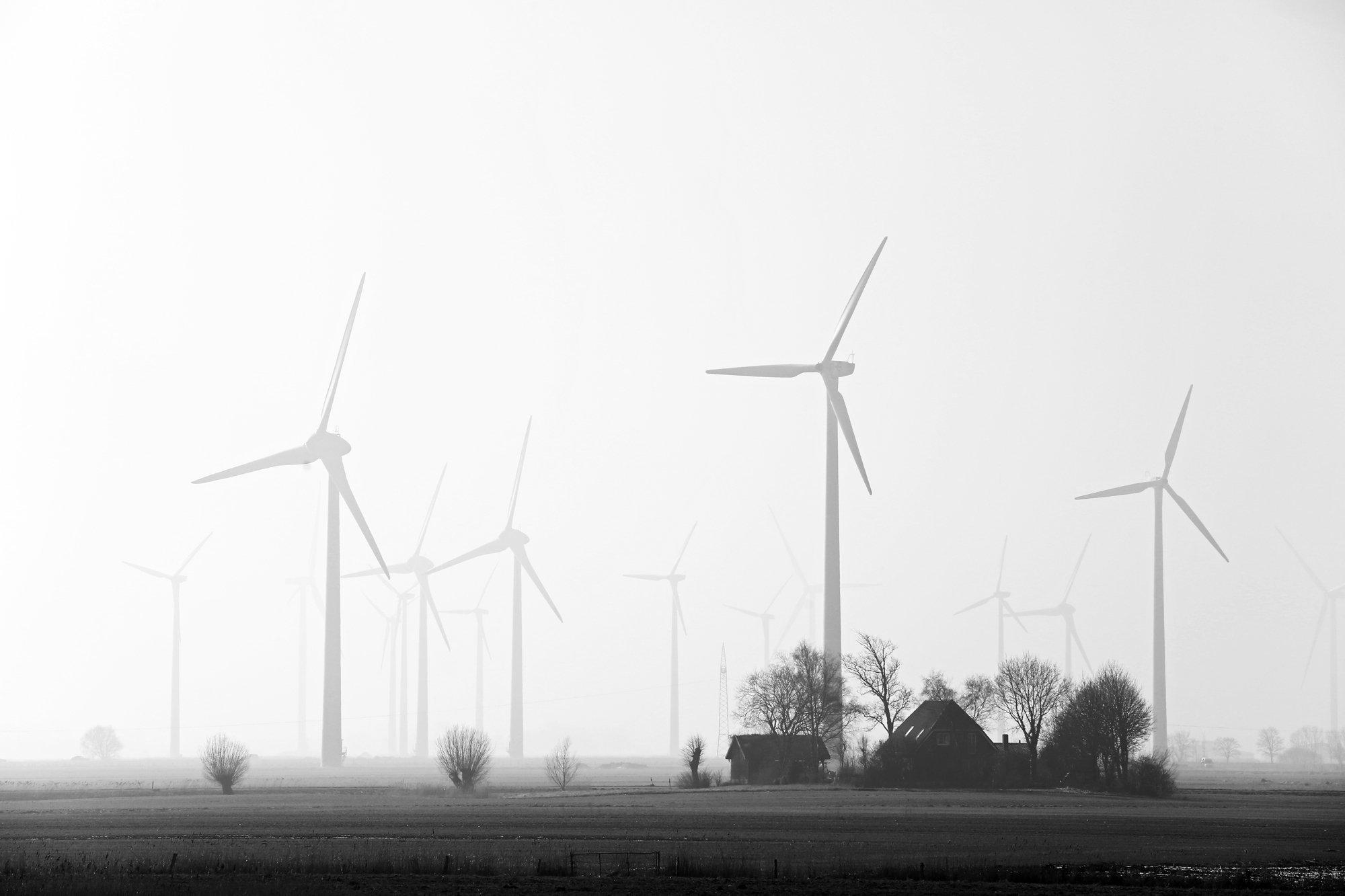 Schwarzweiß-Foto von Windrädern und Bauernhäusern in Norddeutschland