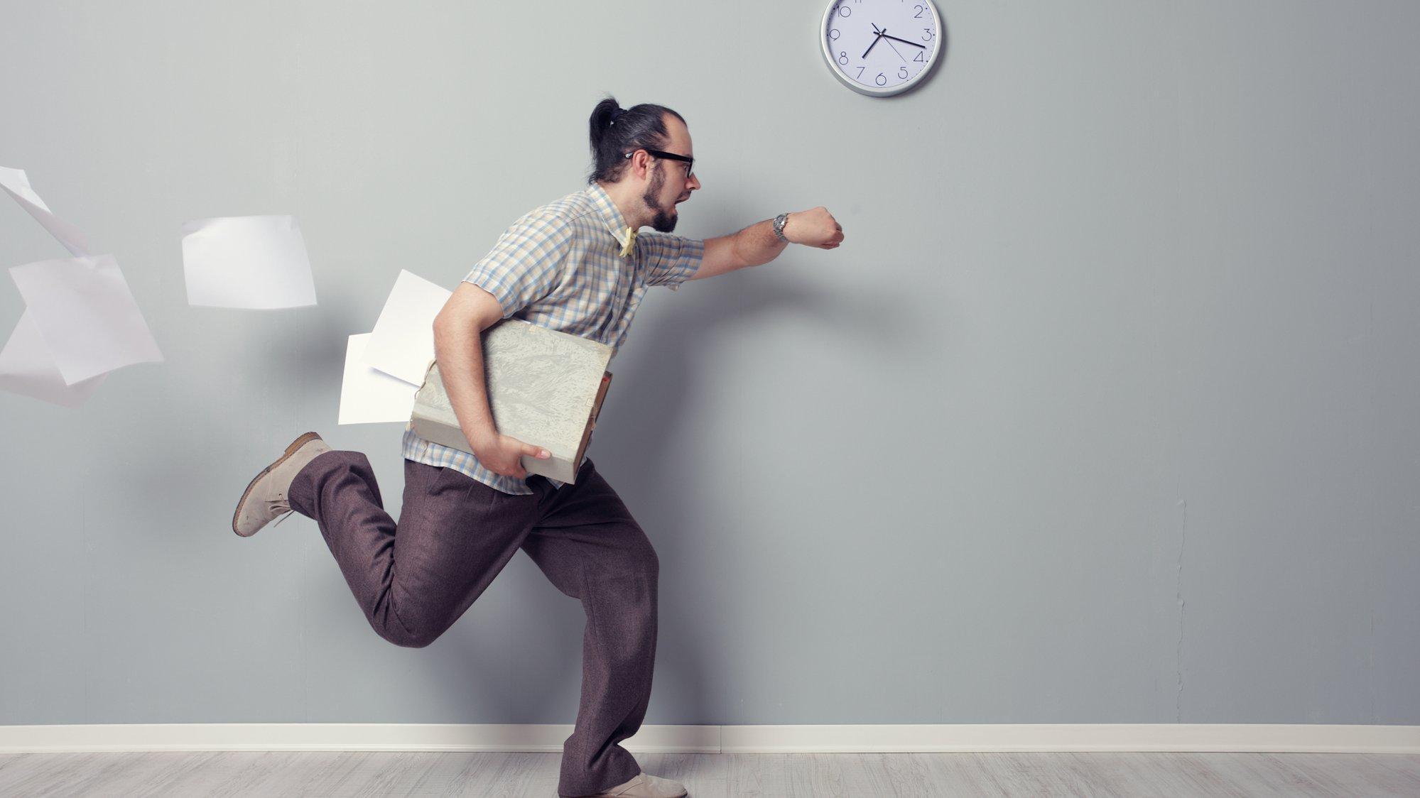 Ein Mann läuft, verliert dabei Arbeitsmaterialien und schaut währenddessen auf die Uhr.