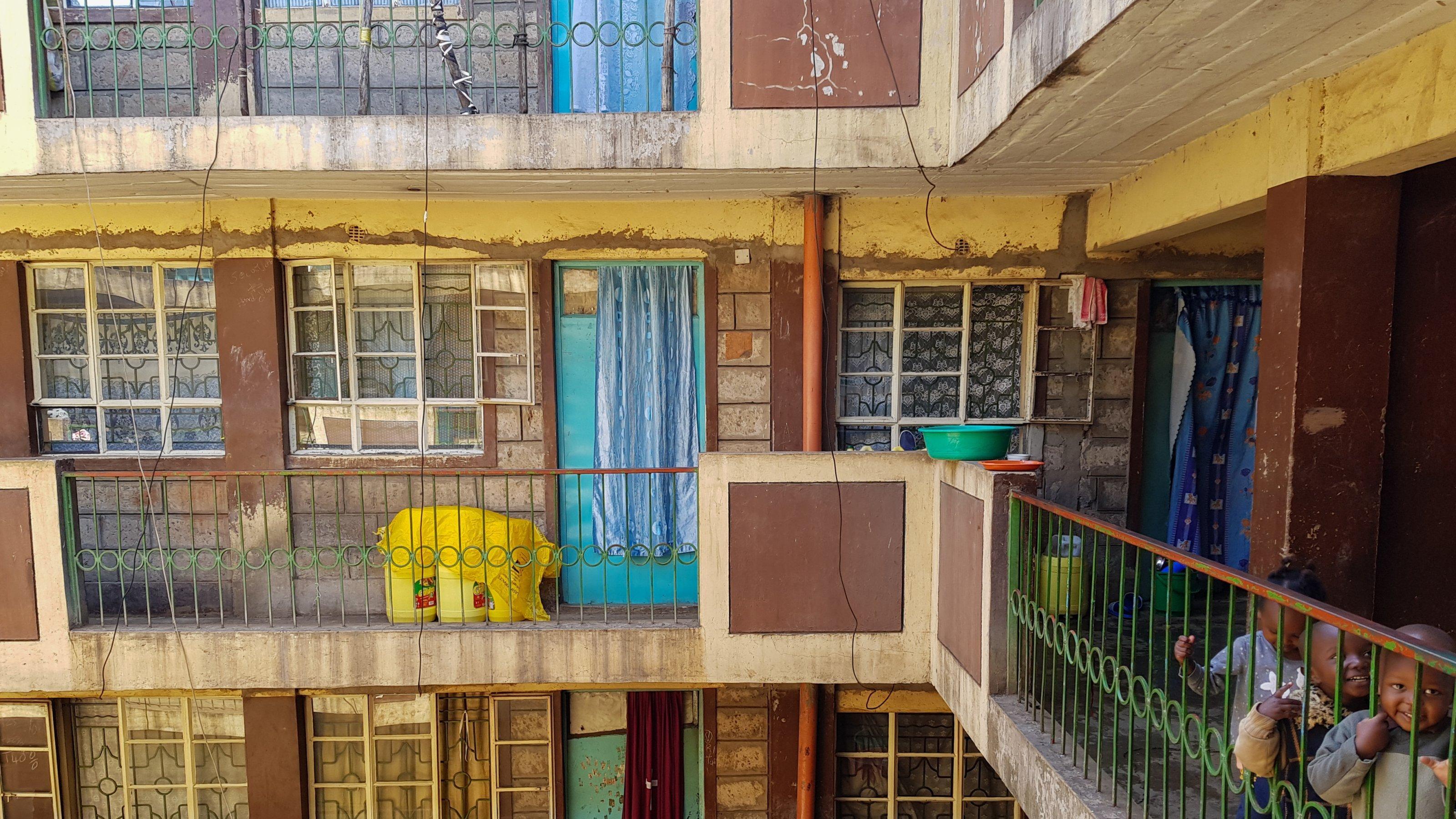 Aufnahme aus dem Innenhof eines Wohnblocks. Rechts am Geländer stehen drei Kinder, die in die Kamera lächeln.