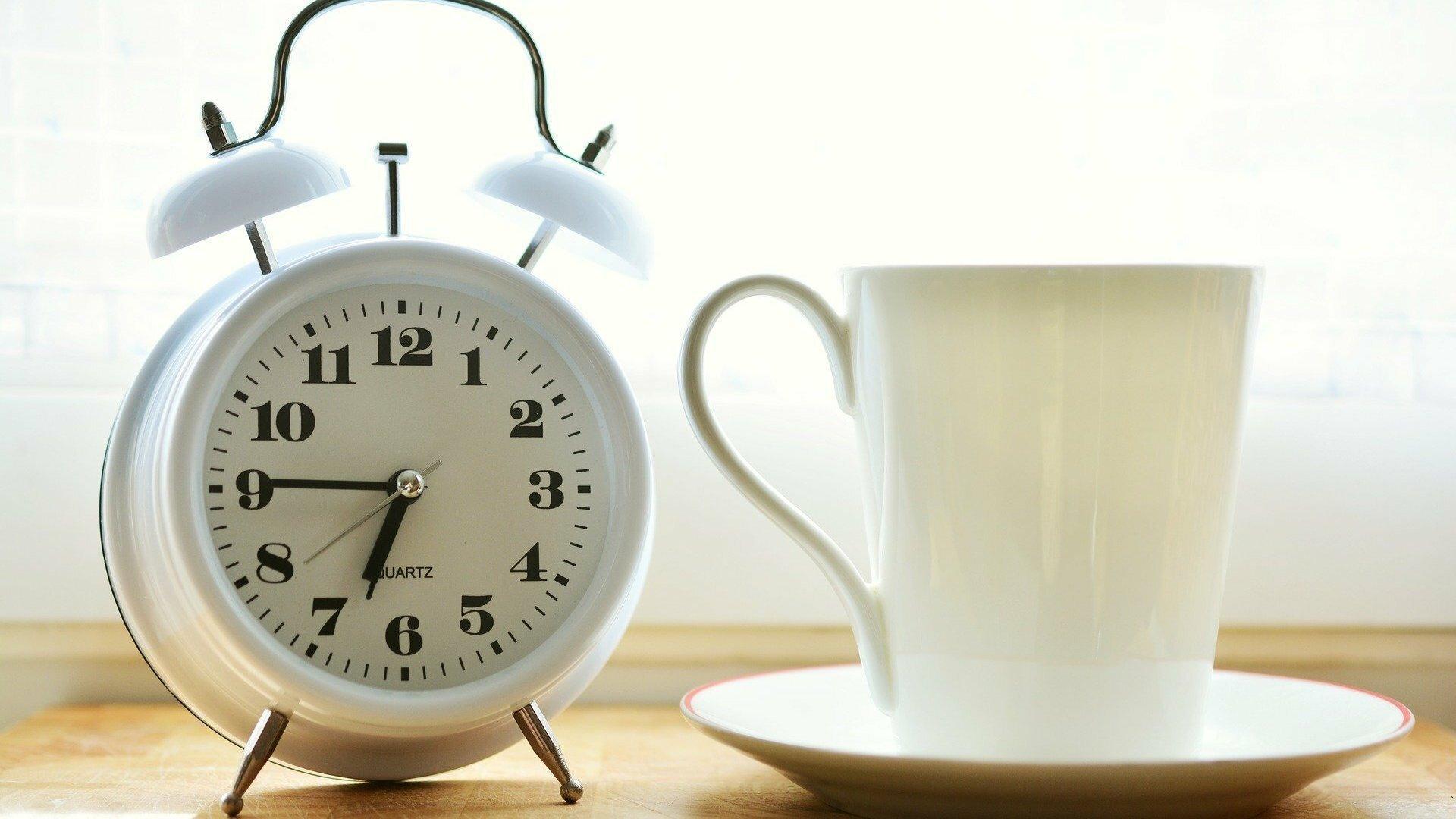 Ein weißer Wecker und eine weiße Kaffeetasse stehen auf einem Tisch.