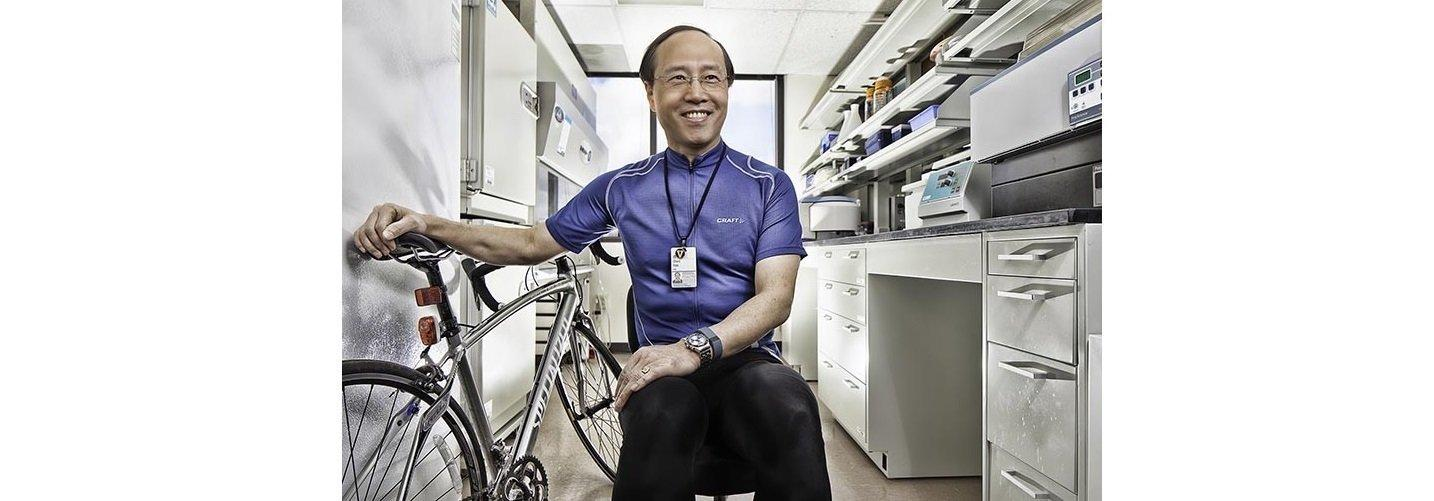 Ein sportlicher mittelalter Wissenschaftler in seinem Labor. Er hat ein Fahrradtrikot an. Neben ihm steht sein Rennrad.