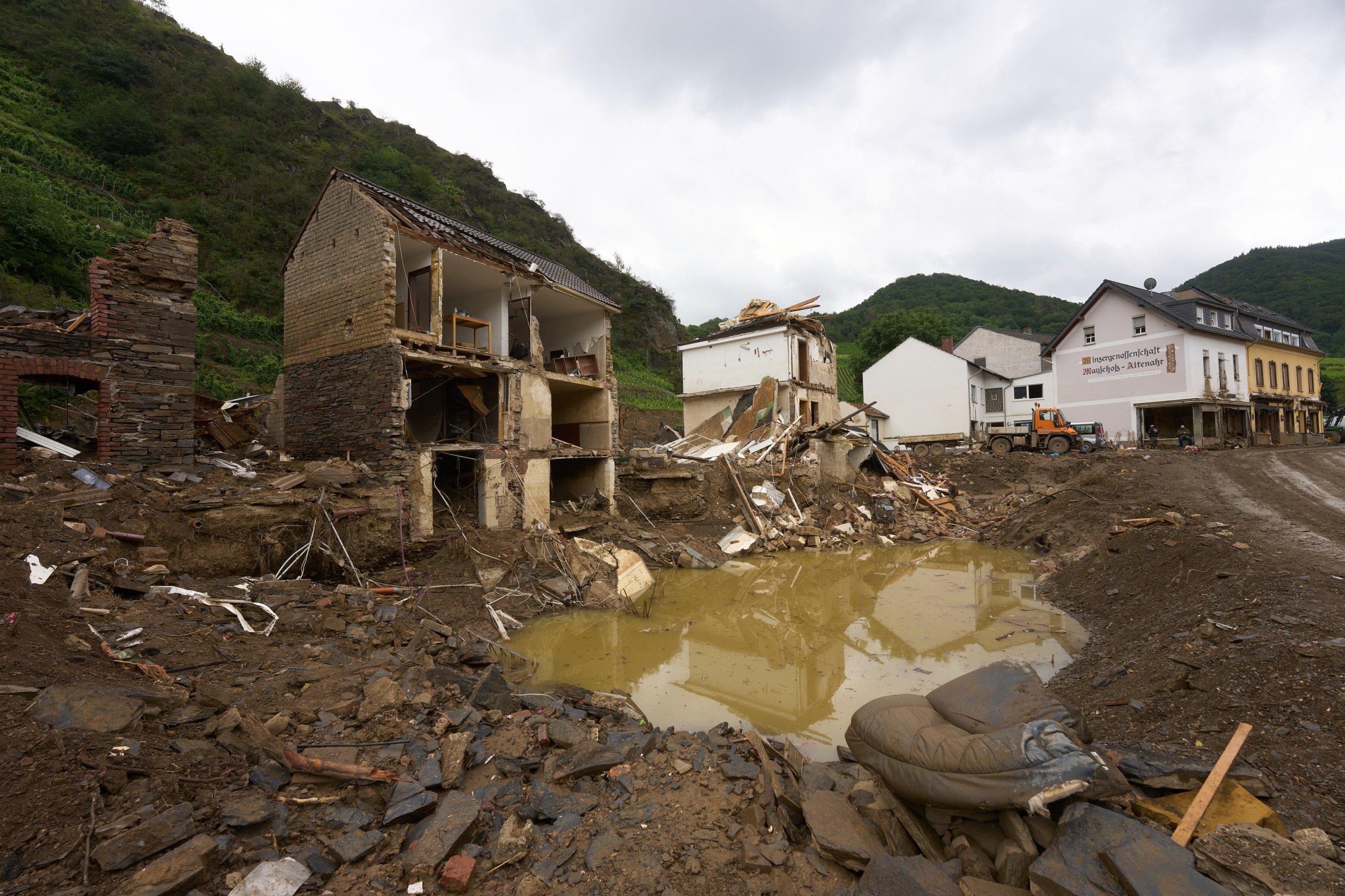 Haus, dessen Vorderfront vom Hochwassers zerstört wurde, im Vordergrund eine kraterförmige Pfutze, gefüllt mit Wasser