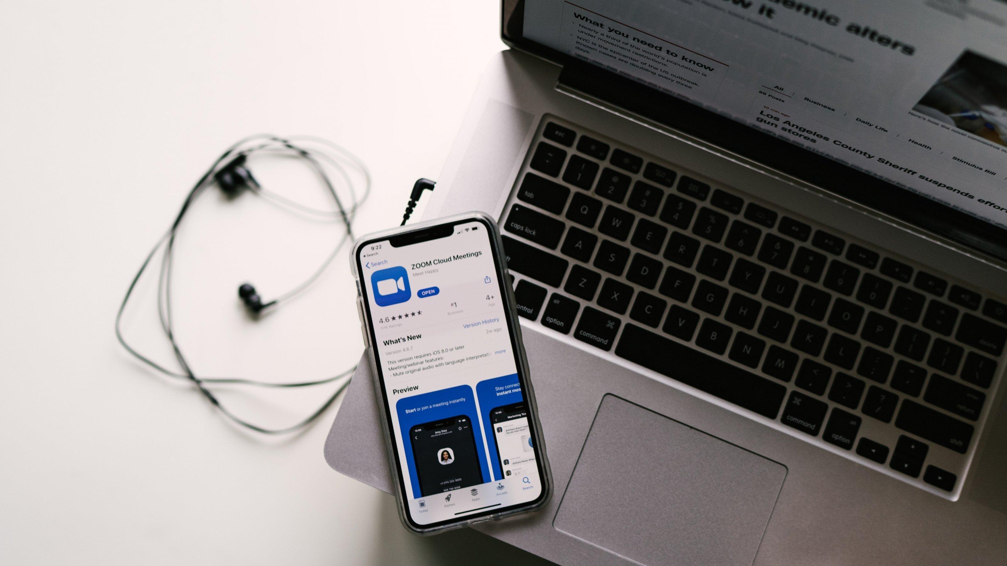 Auf einem Tisch steht ein Laptop mit angeschlossenen Kopfhörern. Auf dem Computer liegt ein Smartphone, auf dem gerade die Zoom-App installiert wird.