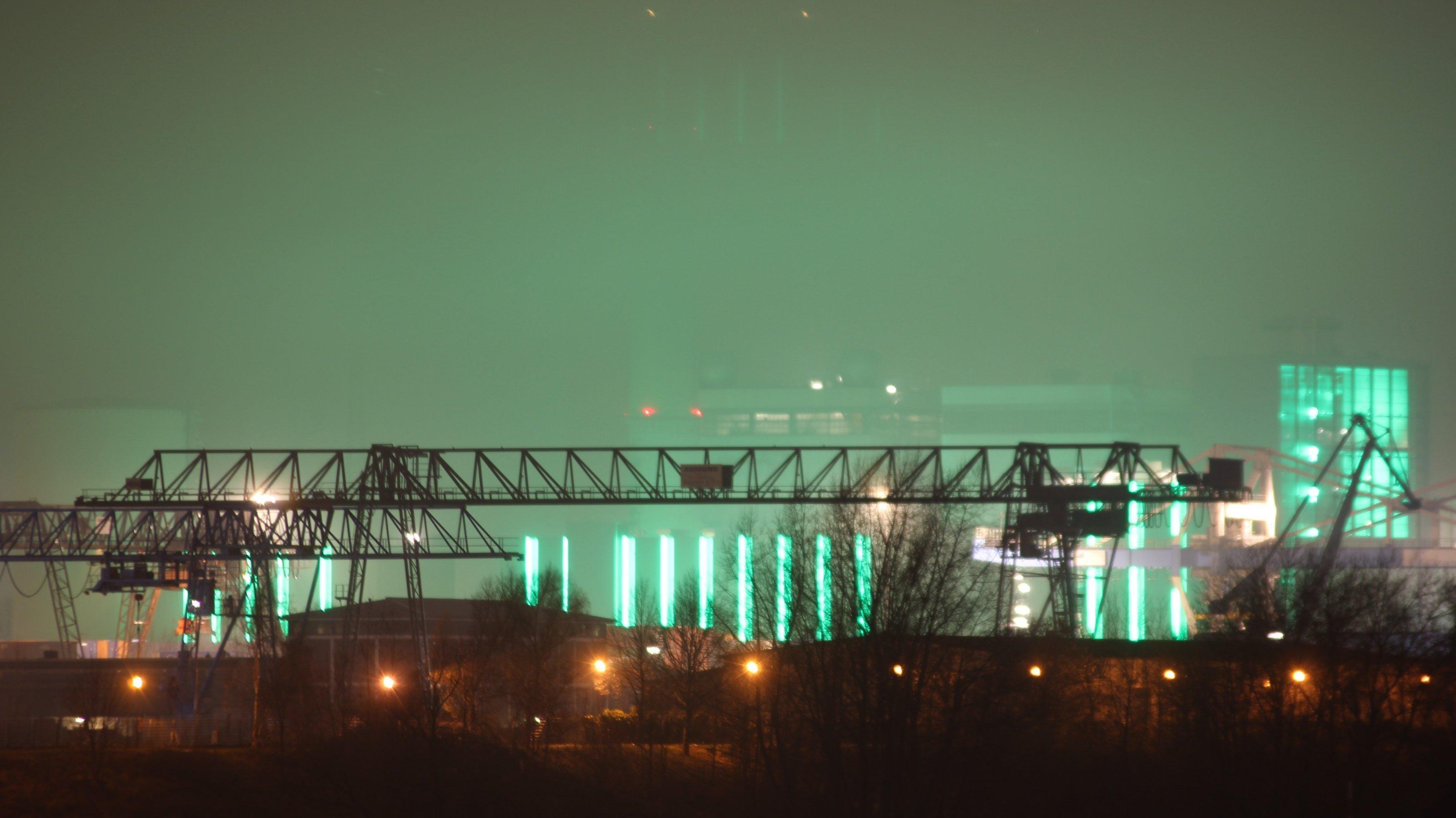 Die grüne Beleuchtung eines Kraftwerks leuchtet eine abendliche Szene am Düsseldorfer Hafen aus.
