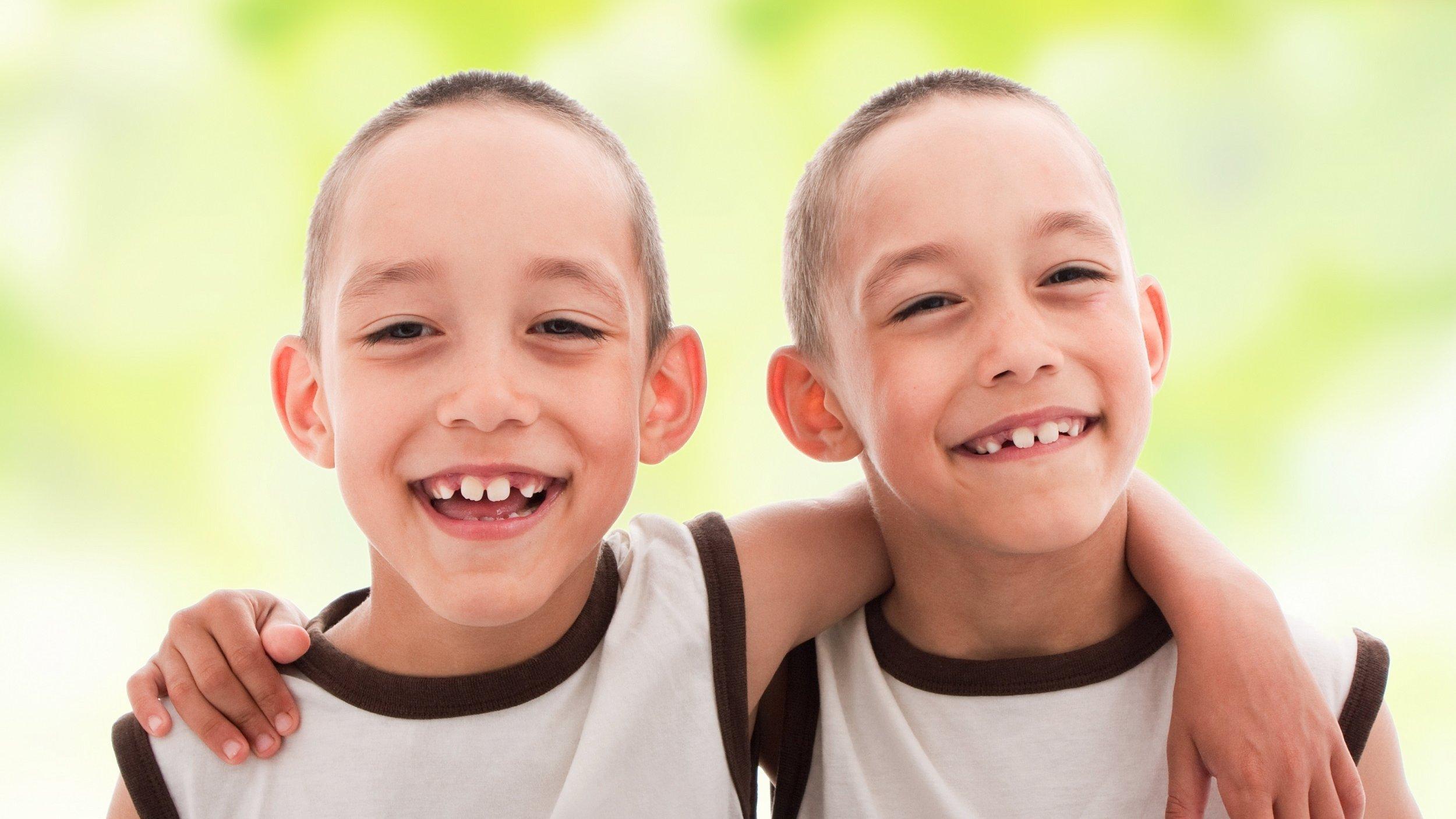 Zwei fröhliche Jungen, die sich so ähnlich sehen, dass es eineiige Zwillinge sein dürften, lächeln in die Kamera.